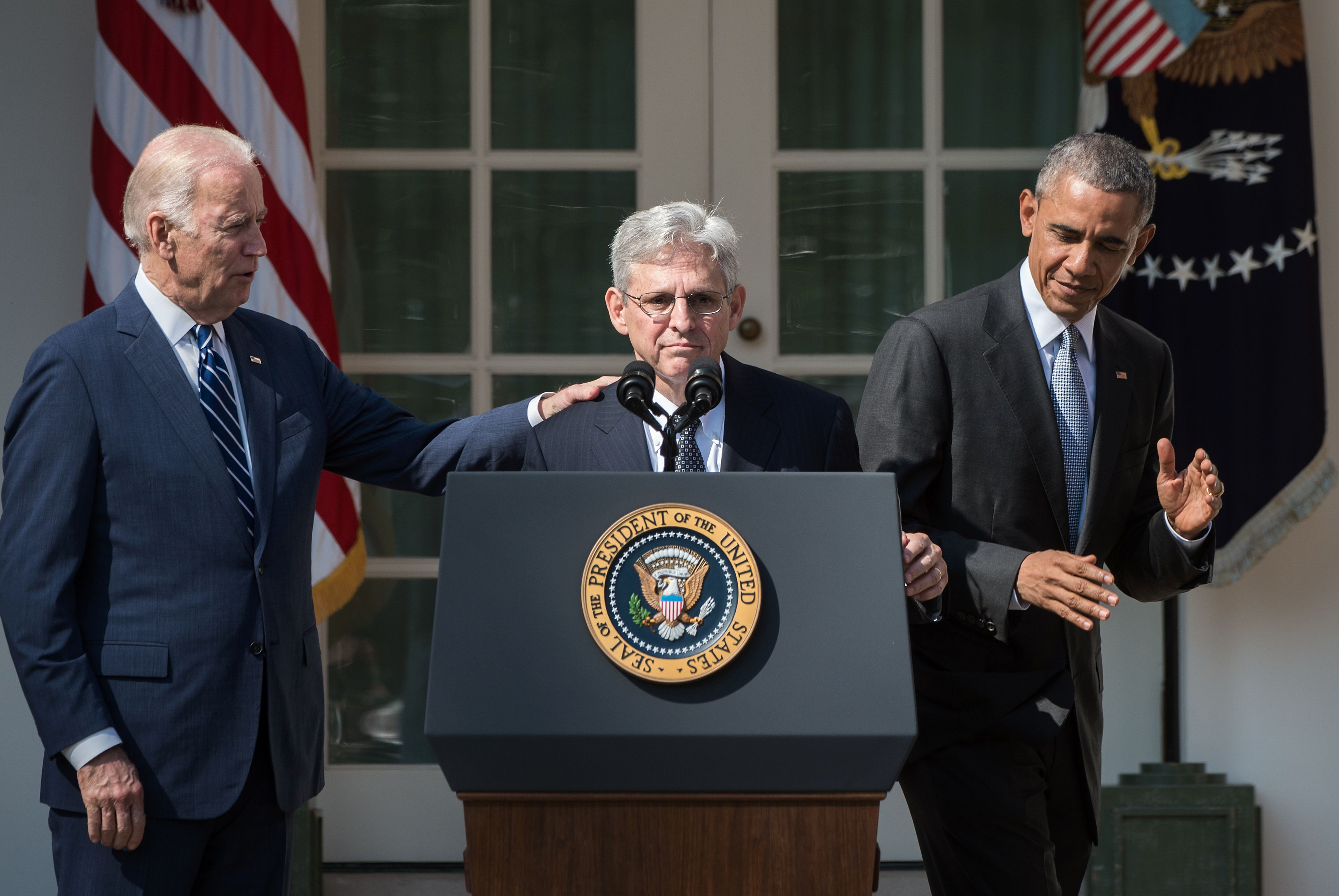 Merrick Garland stands at a lectern. Vice President Joe Biden stands with his hand on Garland's shoulder. President Barack Obama stands on Garland's other side.