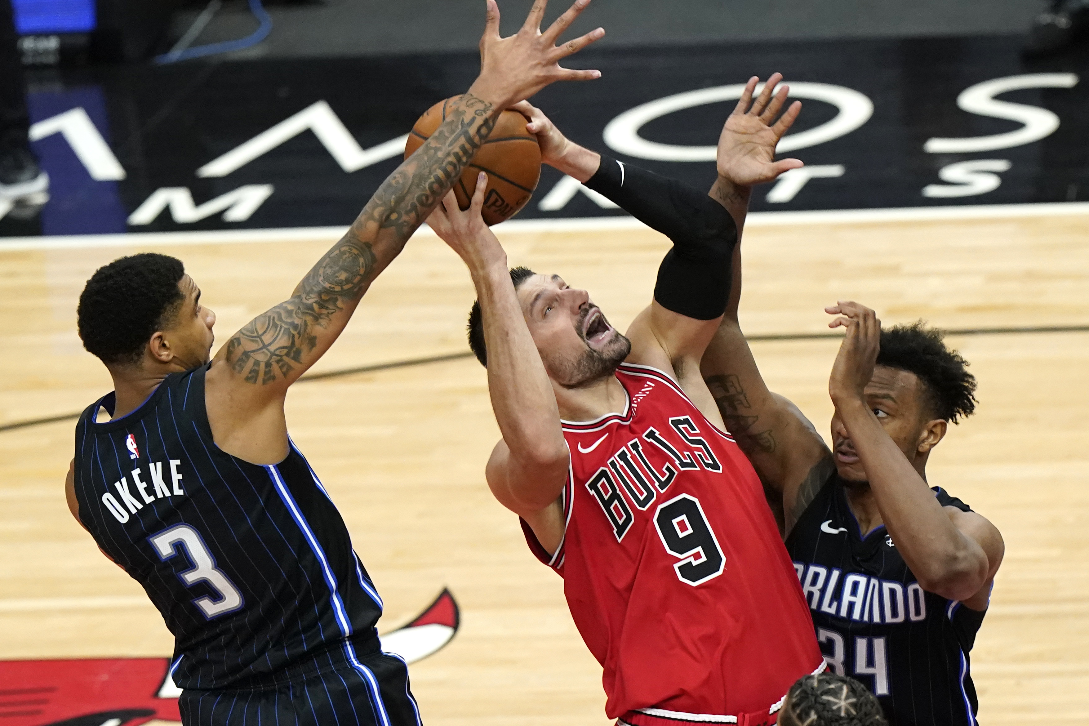 Bulls center Nikola Vucevic takes a shot as Magic forward Chuma Okeke and center Wendell Carter Jr. defend during the second half Wednesday night.