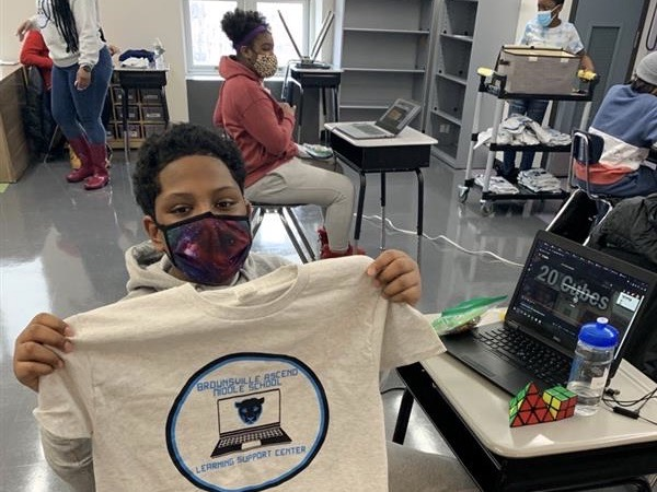 Seventh grader Jamari Adams proudly displays a shirt from the Brownsville Ascend Middle School.