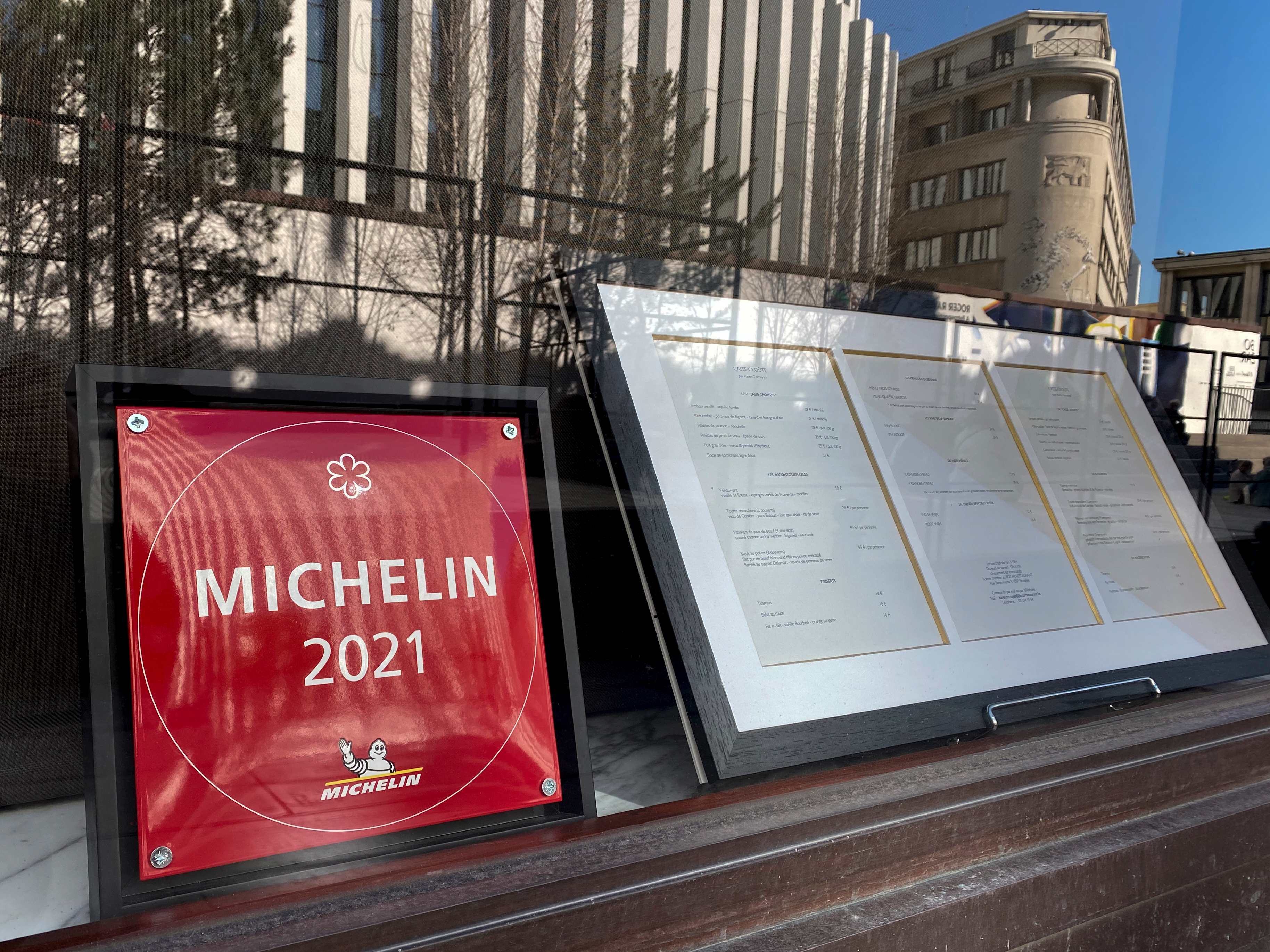 """A red square sign reading """"michelin 2021"""" framed in the window of a restaurant, with a framed menu beside it"""
