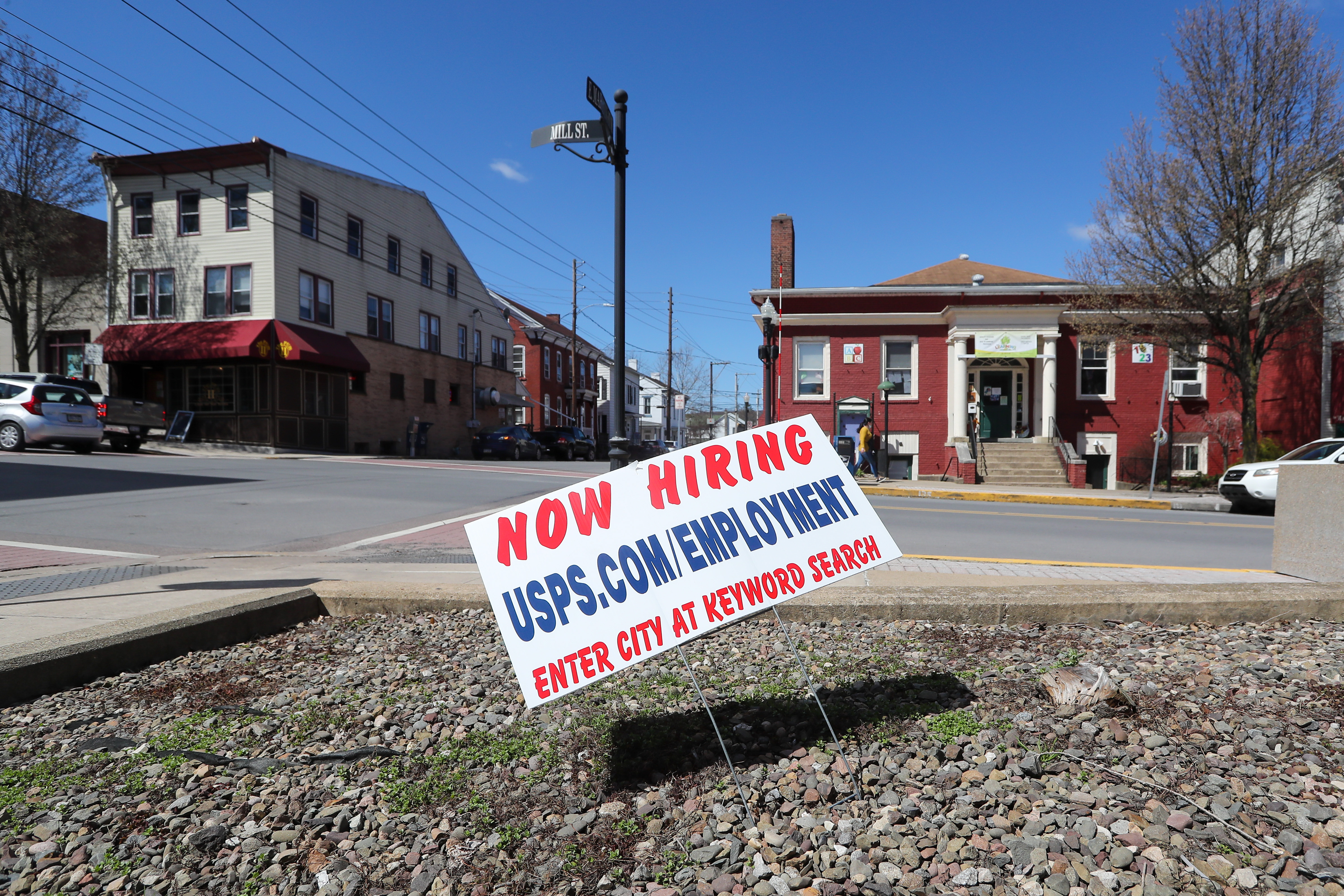 "In a vacant lot, behind which is a red-painted building, there is a sign reading ""Now hiring usps.com/employment."""