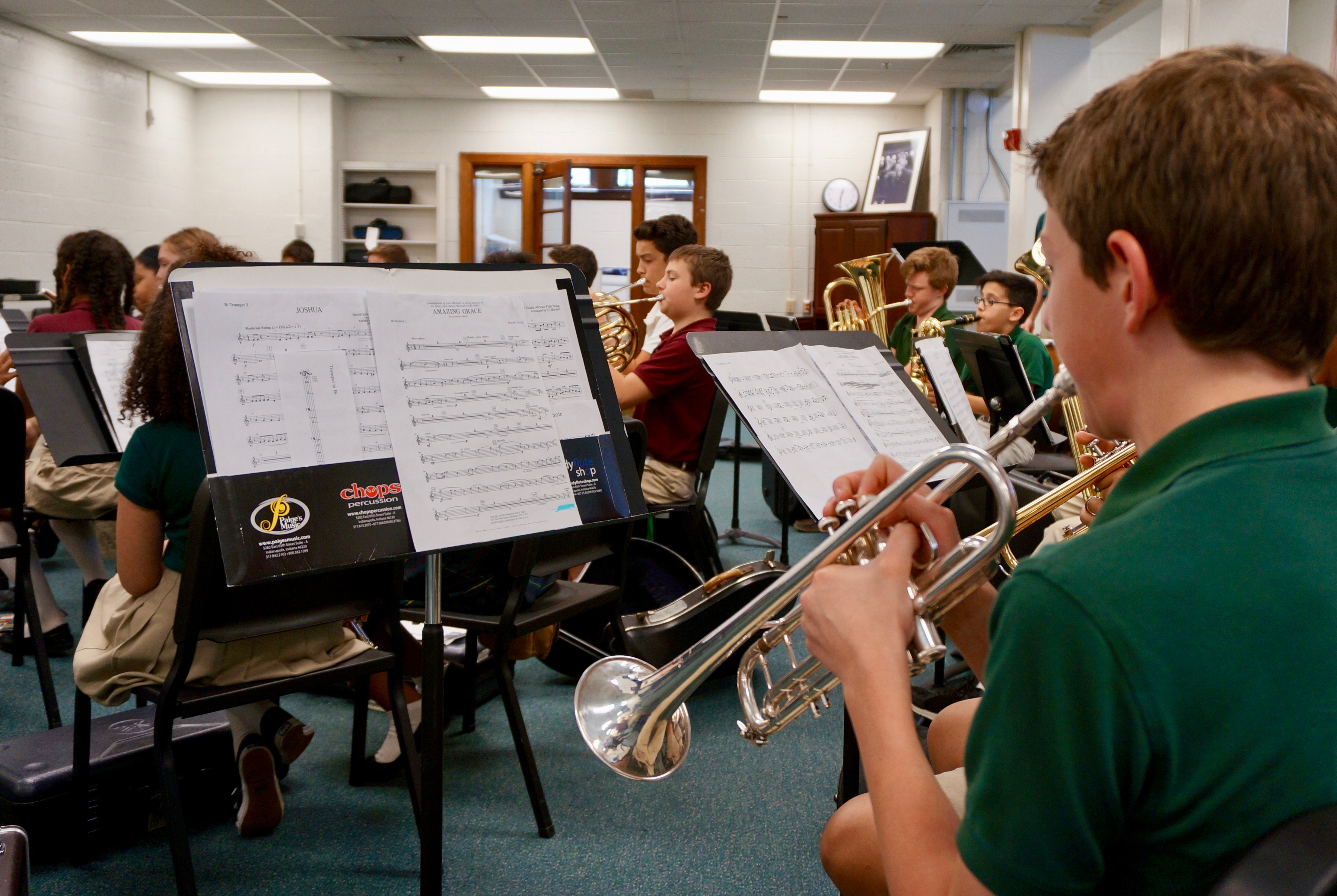 Middle school students practice the trumpet, tuba, French horn and other instruments in a classroom