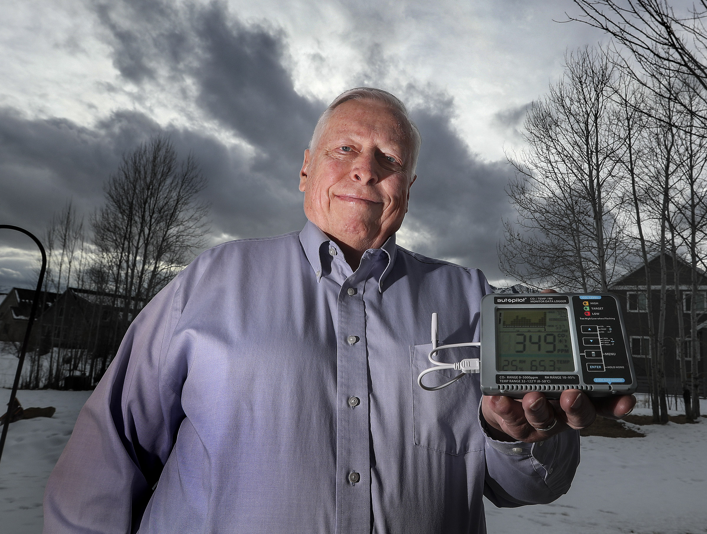 Bill Pekny poses for a photo as he uses a monitor to check carbon dioxide levels outside of his home in Midway on Tuesday, Feb. 2, 2021. Pekny is a local author and scientist and agrees the climate is warming, but he says that we are in a normal cycle of warming and panic is unwarranted.