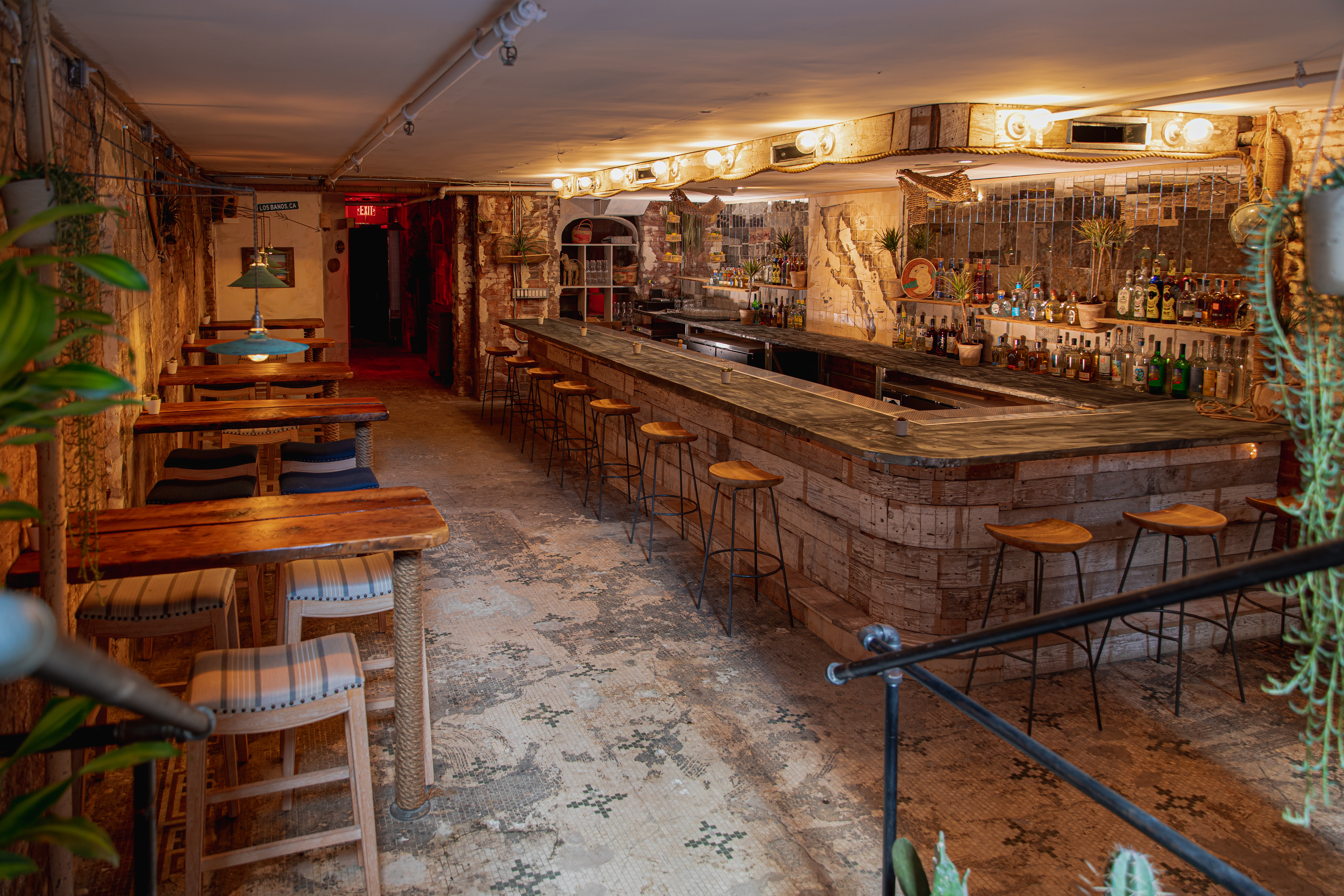 An underground bar with several wooden tables and chairs, along with a long bar countertop to the right where there are several stools