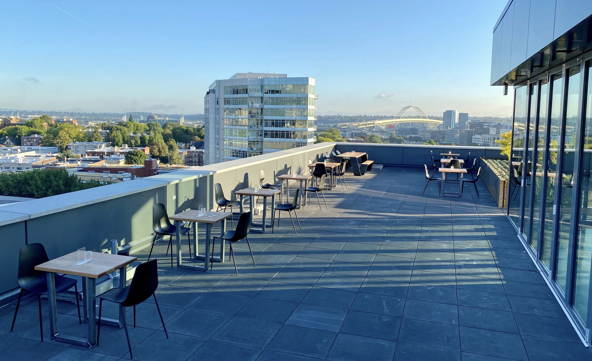 Tables and chairs sit out on a patio with a view of Portland