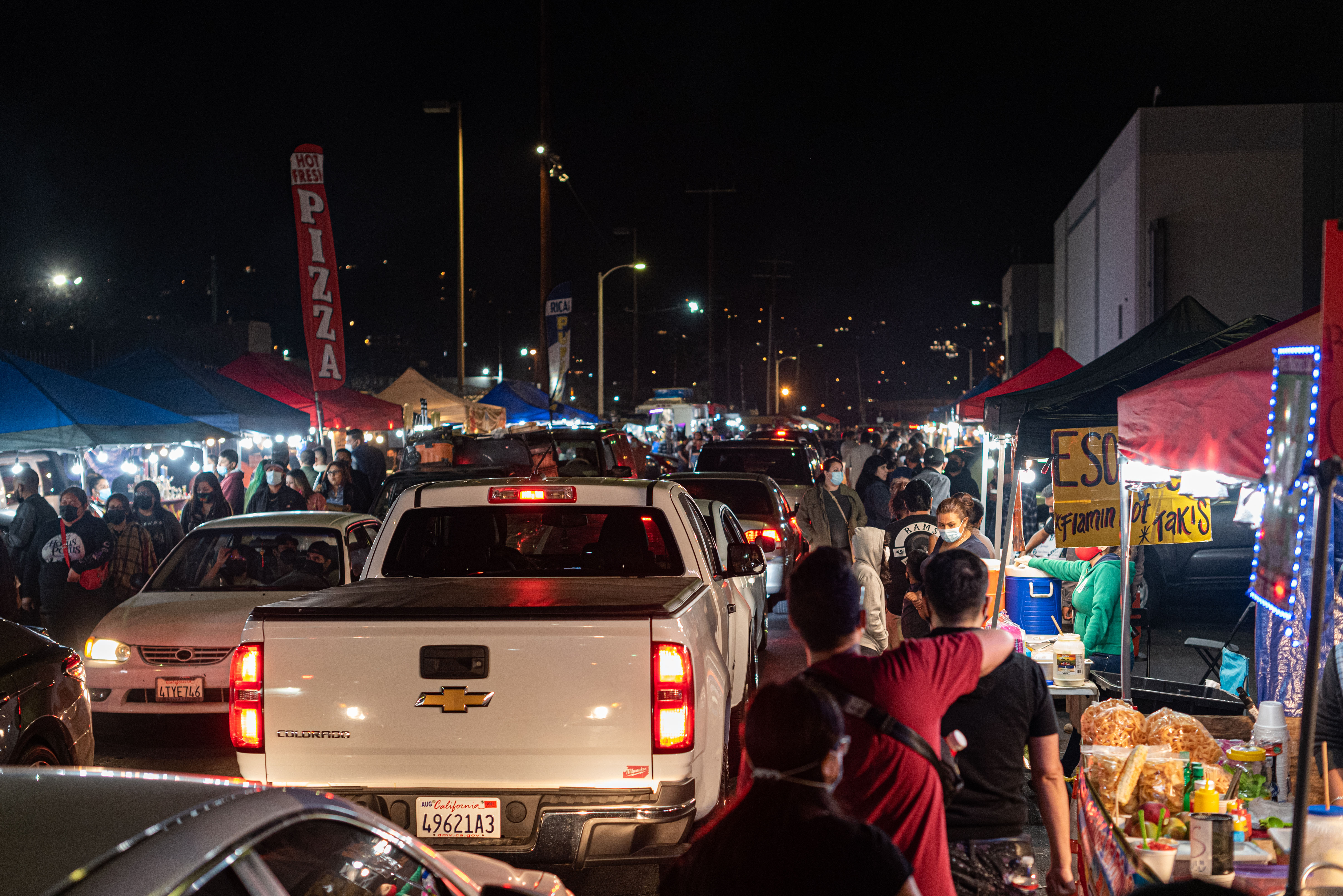 Cars and brake lights inside of a very busy night market.