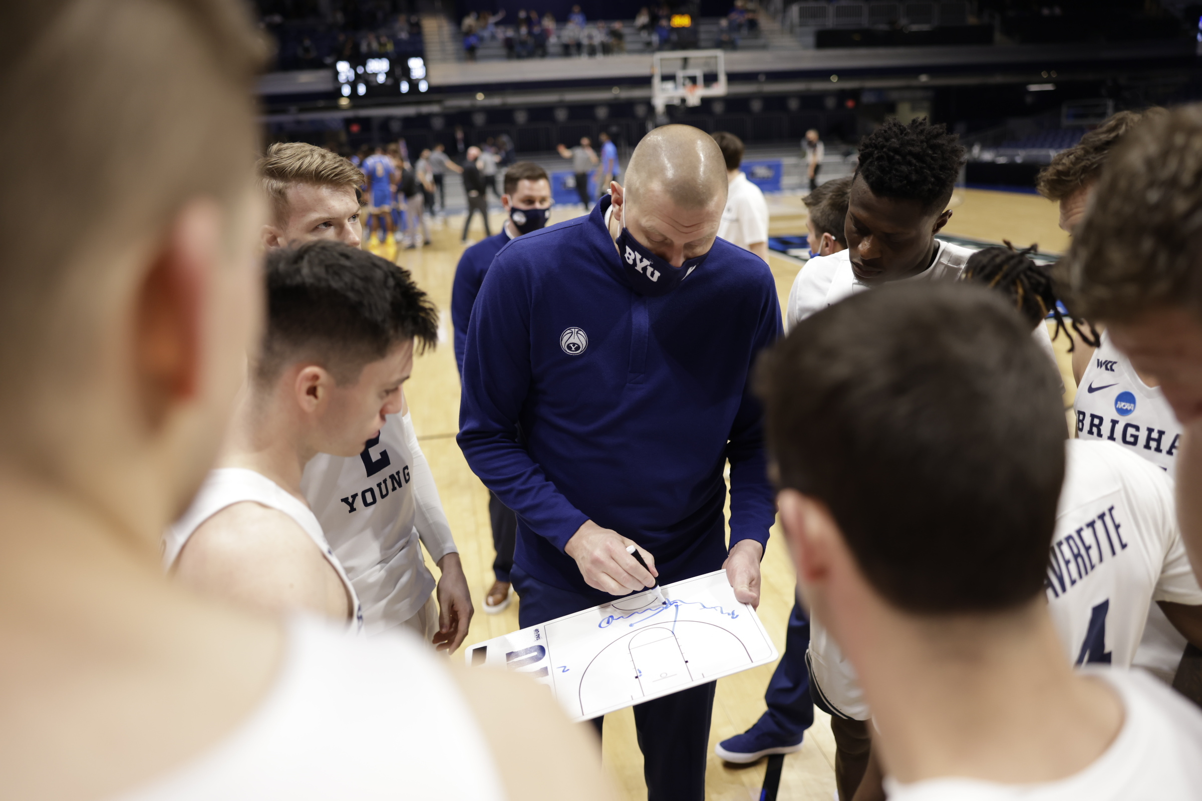 BYU coach Mark Pope, center, is surrounded by his players during a timeout in the Cougars' 73-62 loss to UCLA in the NCAA Tournament first round at Hinkle Fieldhouse in Indianapolis on Saturday, March 20, 2021.