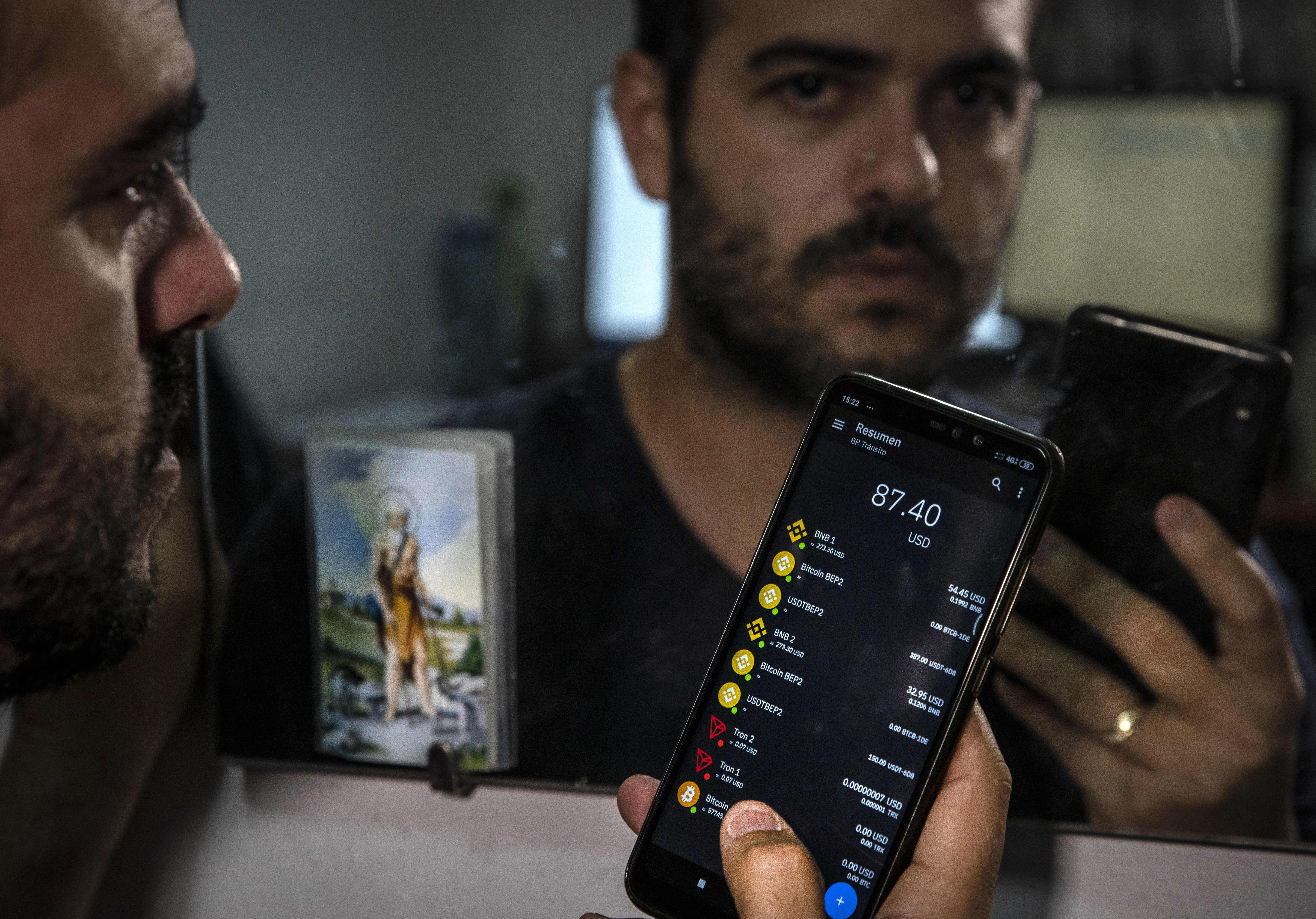 Eyonys González poses for the photo with his bitcoin wallet at his home in Havana, Cuba, Monday, March 29, 2021.