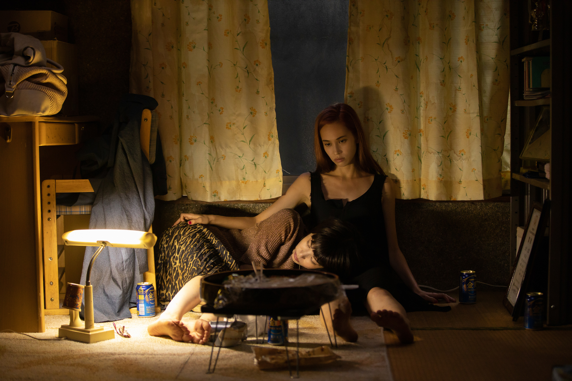 Kiko Mizuhara and Honami Satô sit together in a moody, underlit room in Ride or Die