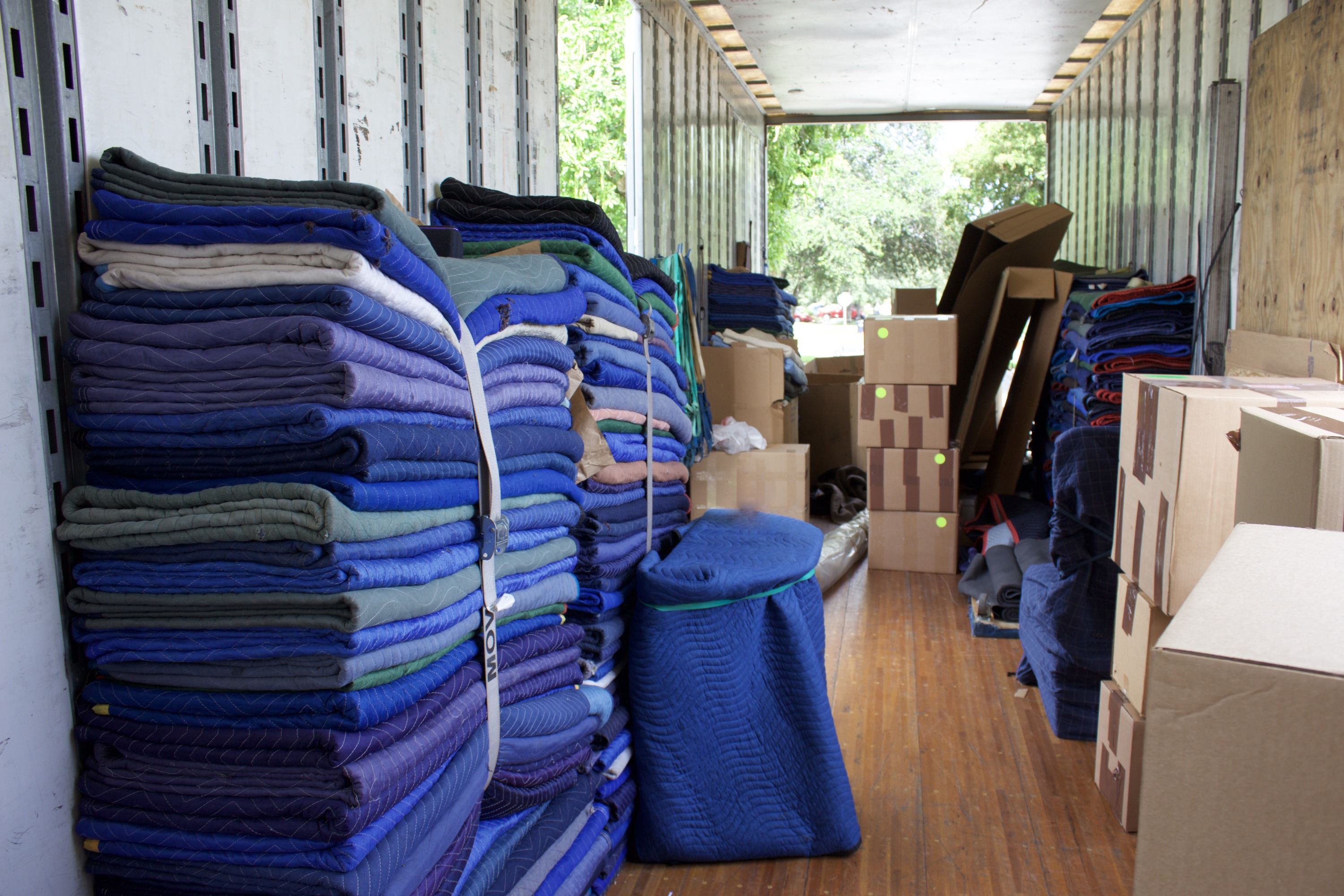 Interior of a moving truck with blue protective cloths and brown cardboard boxes.