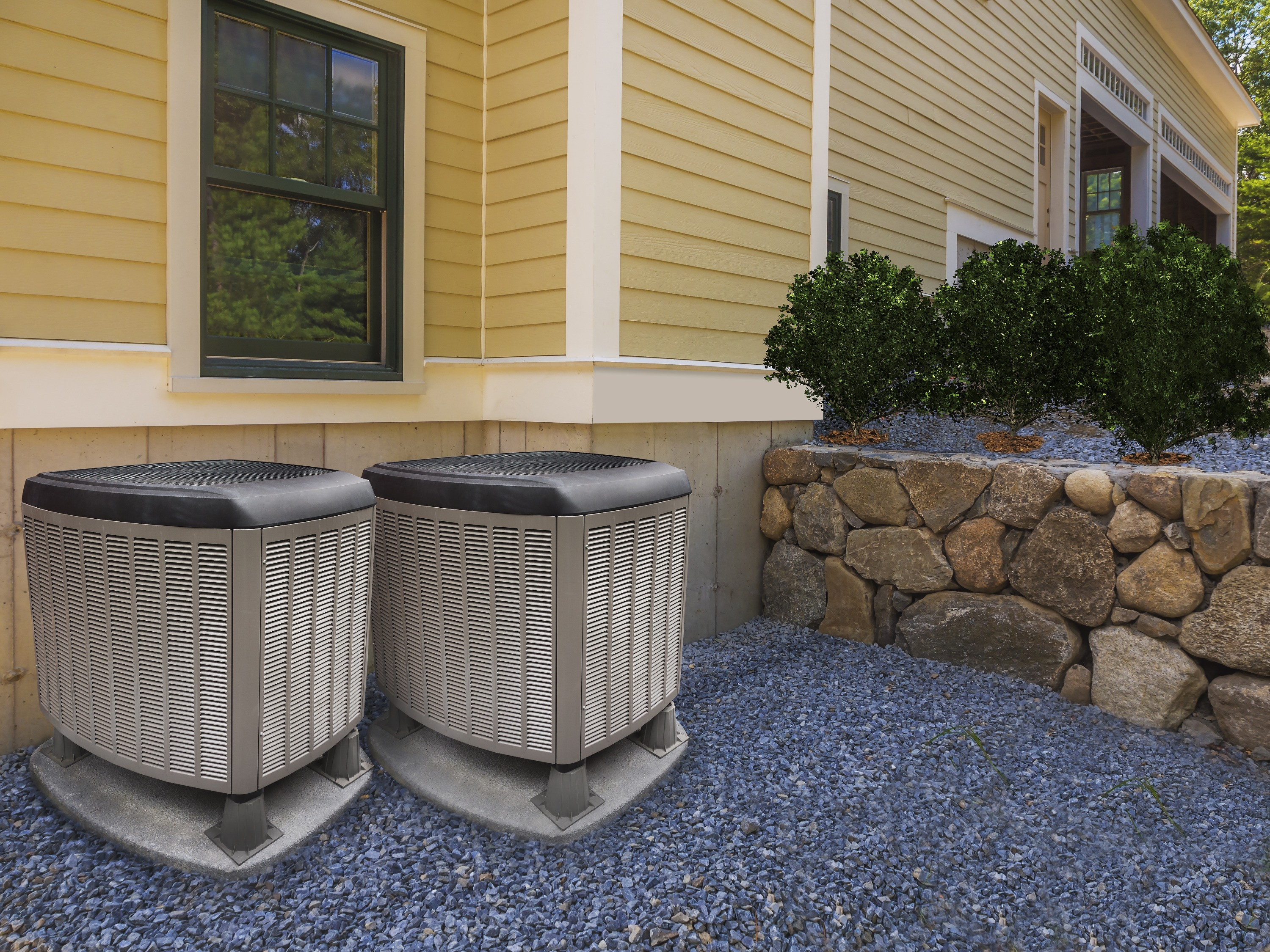 Two heat pumps on the exterior of a yellow home near a stone wall.