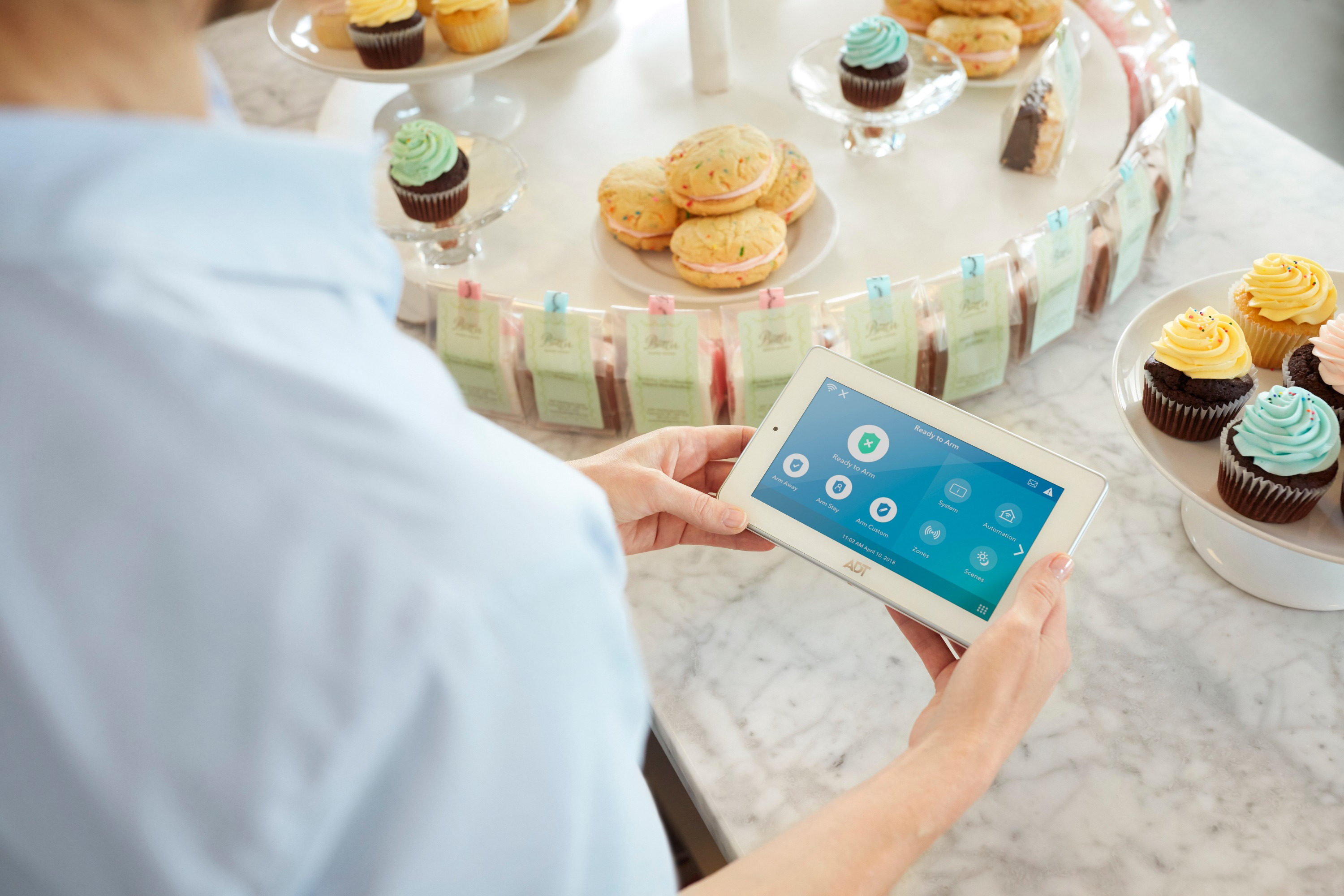 A person wearing a light blue shirt holds an ADT home security device while standing near a display of yellow and blue cupcakes.