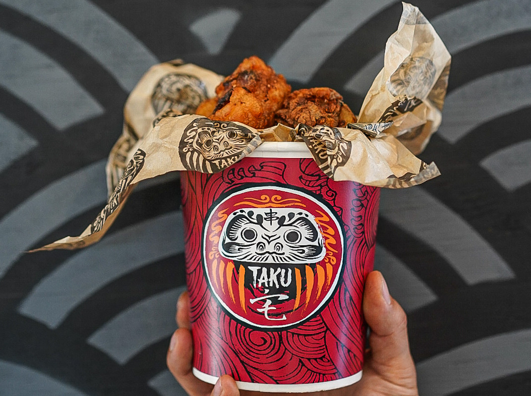 A paper takeout bucket filled with karaage, with a label displaying the name of the restaurant Taku