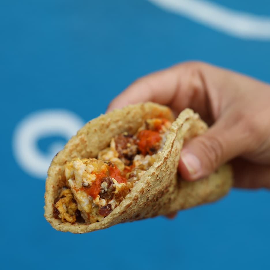 A hand holding a folded taco with eggs and chorizo in front of a blue background