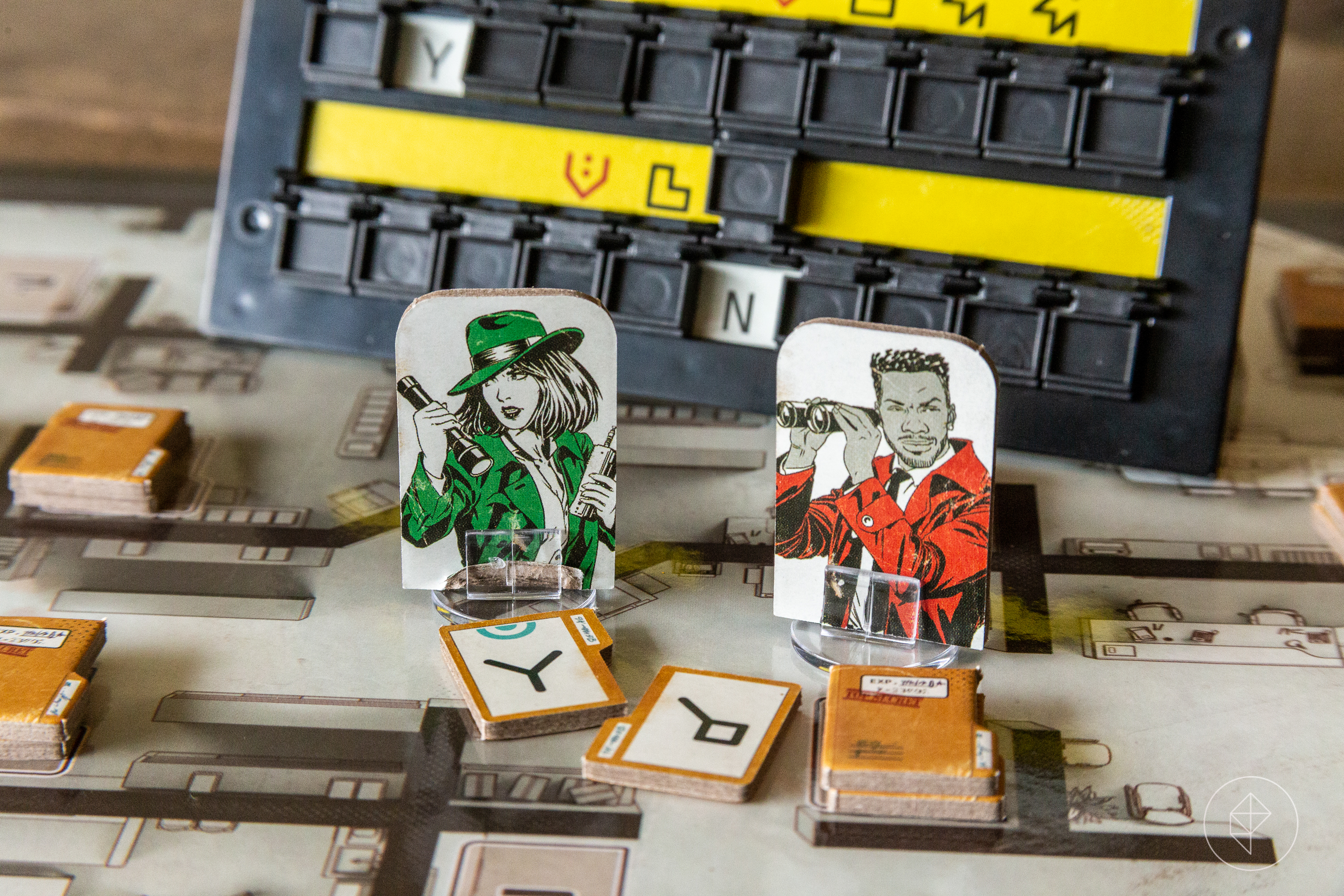 Two player pawns from The Initiative. In the foreground, packets of intel. In the background, a cipher solving machine.