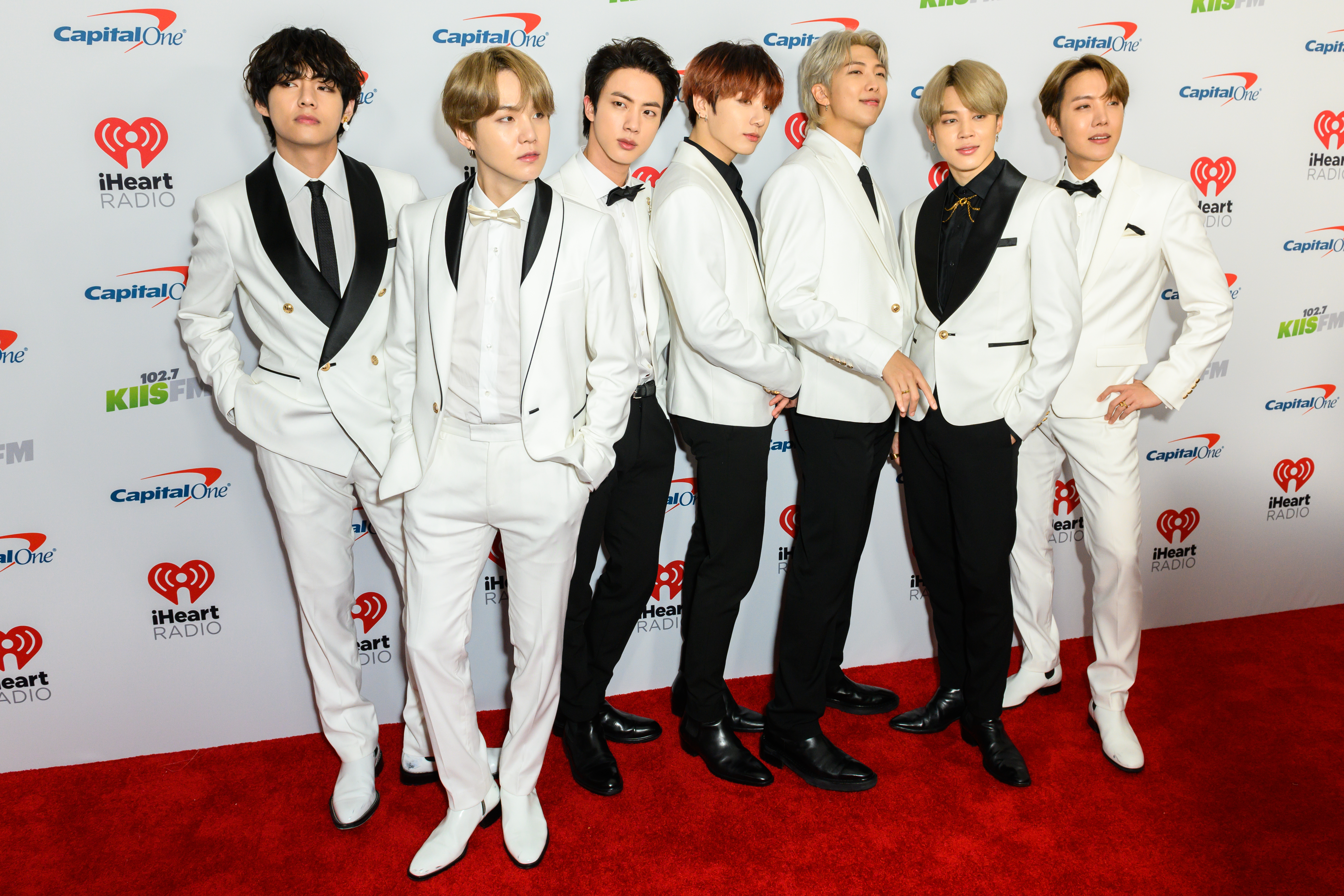All seven members of BTS dressed in white suits on the red carpet.