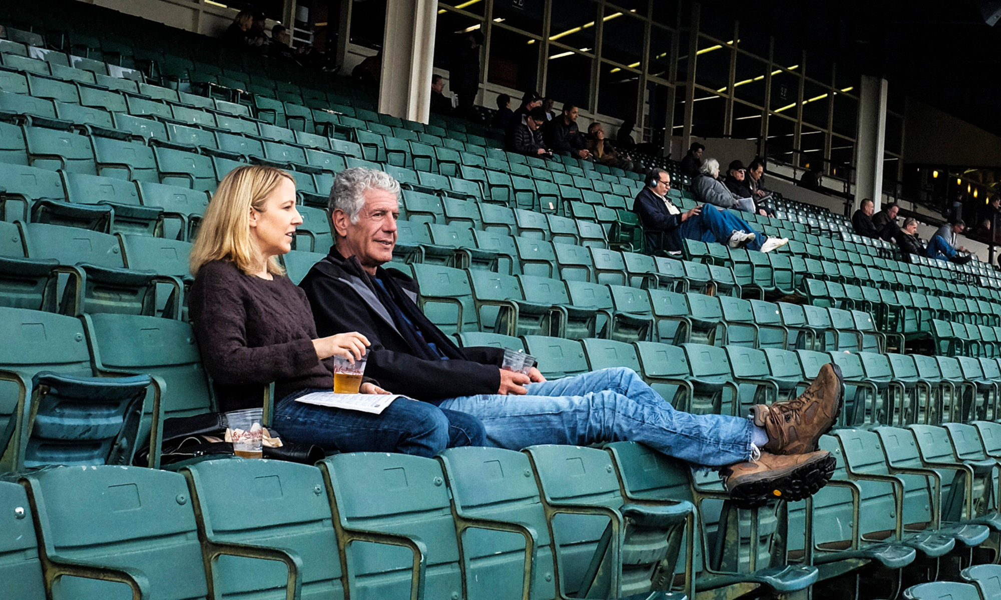 A woman and a man sit in green bleacher seats