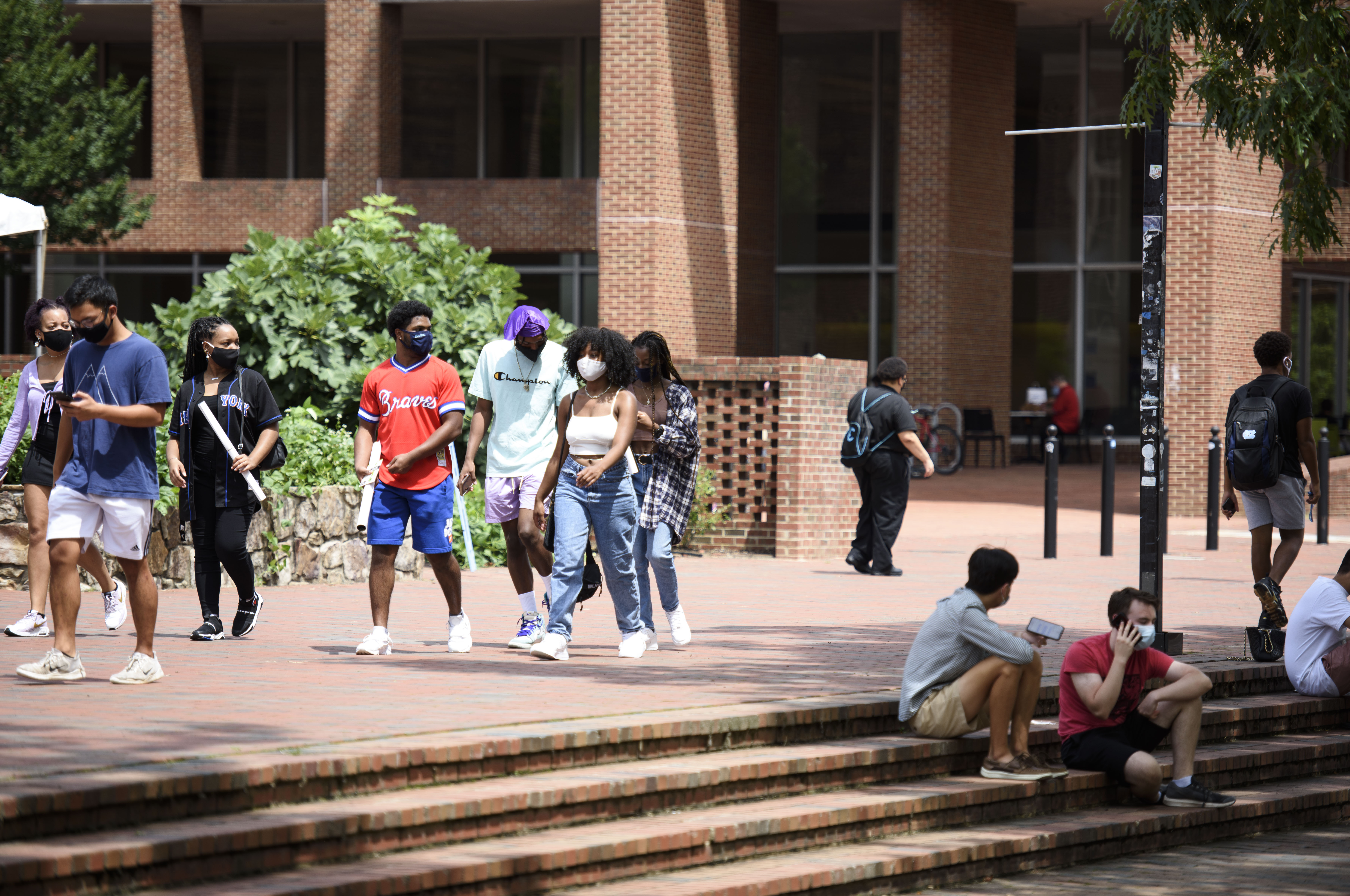 Small groups of students walk on a university campus plaza, with a building in the background. An handful of students sit on the steps of the plaza.