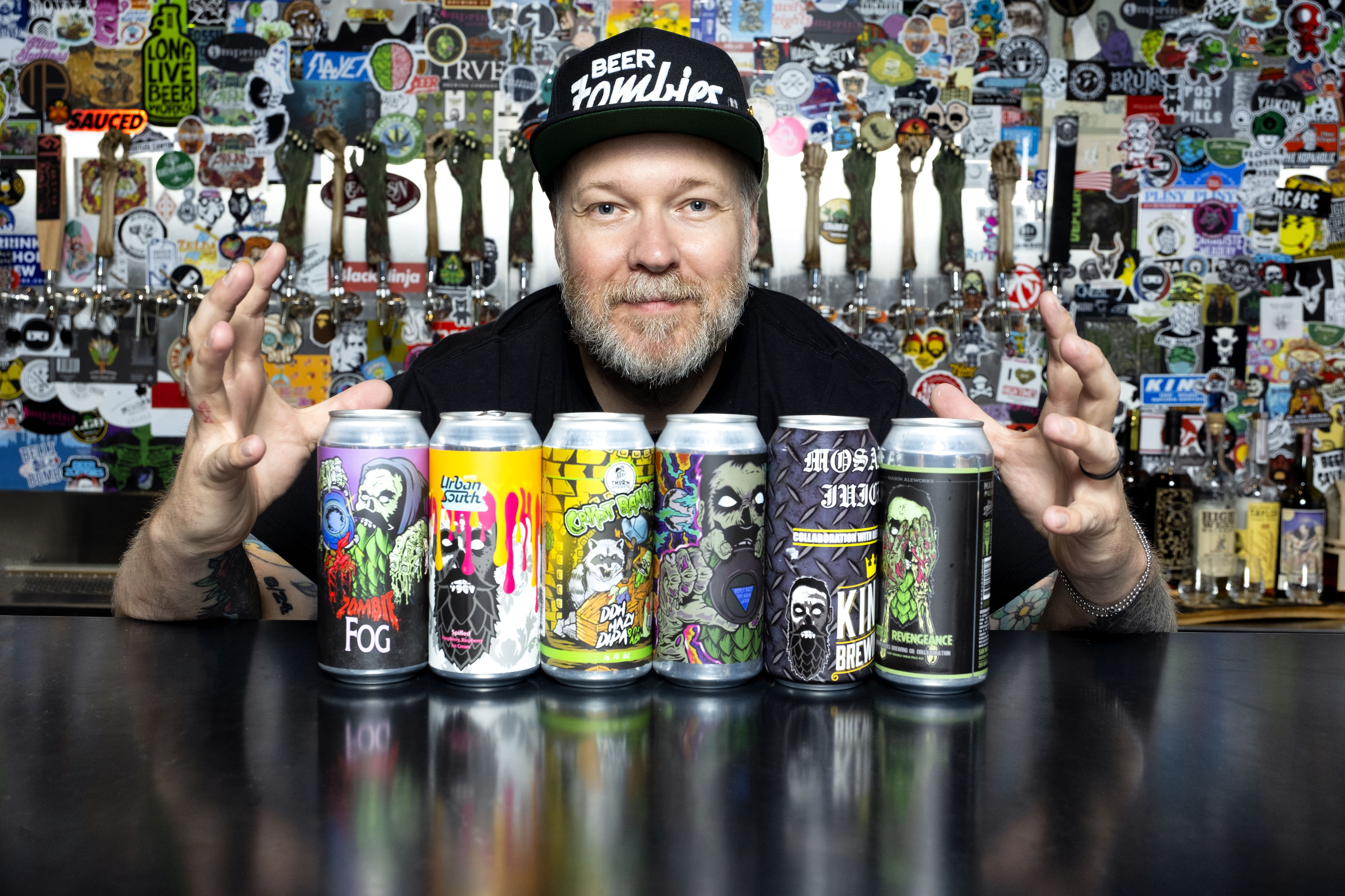 A man holds his hands on either side of six beer cans
