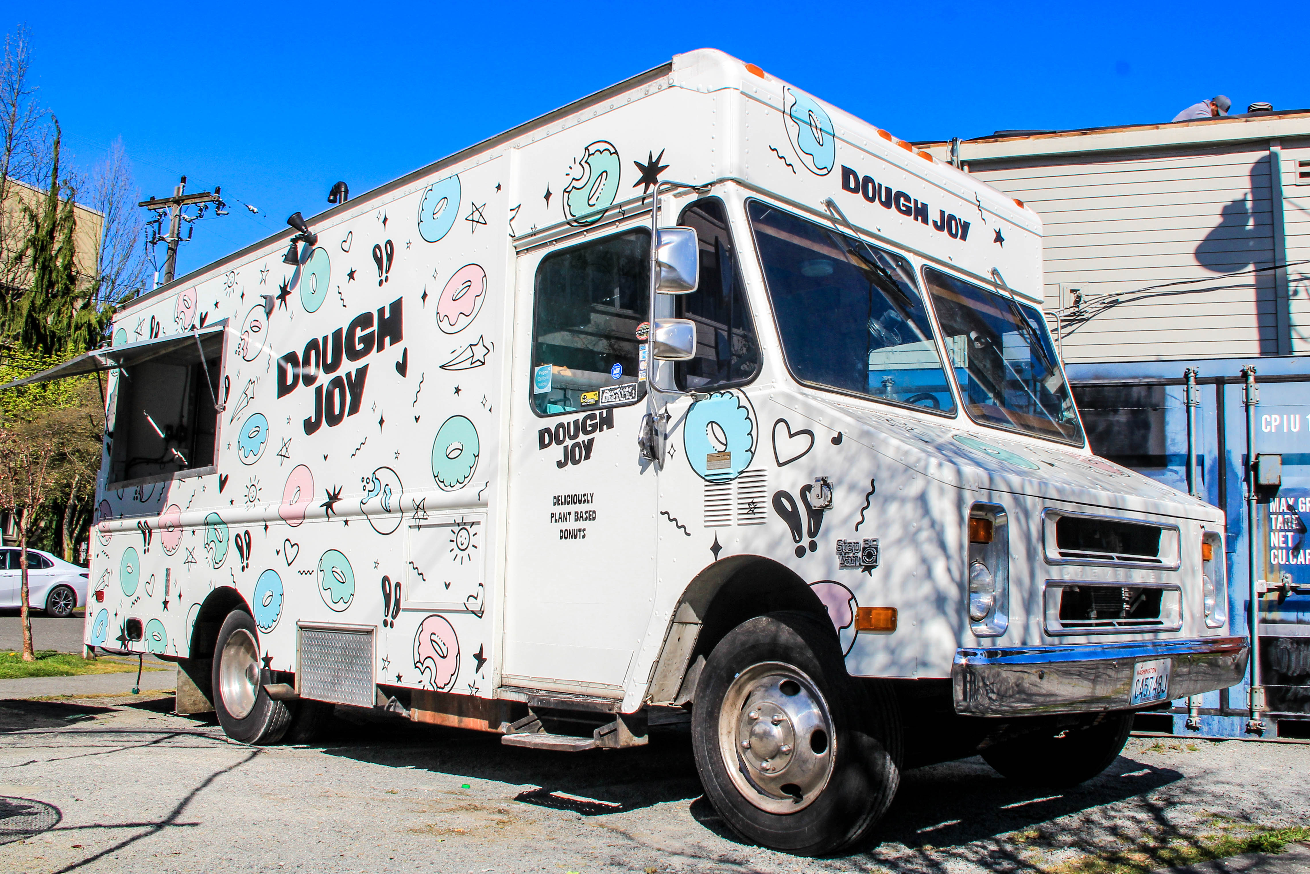 The colorful Dough Joy food truck, painted with various doughnuts on the side along with the business's name