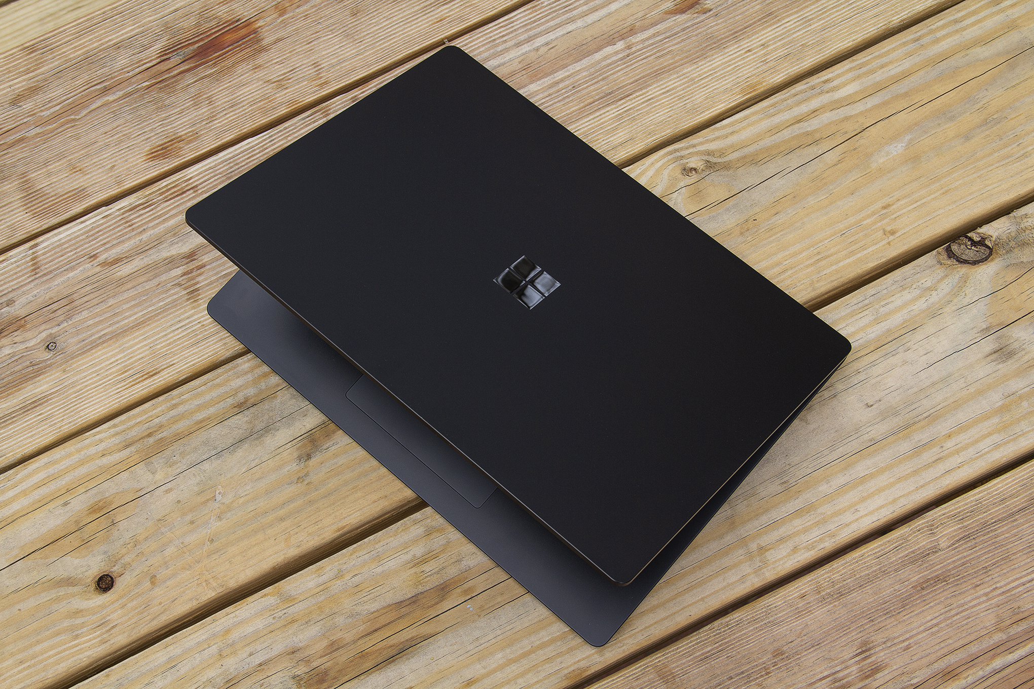 The 15-inch Surface Laptop 4 half open on a picnic table, seen from above.