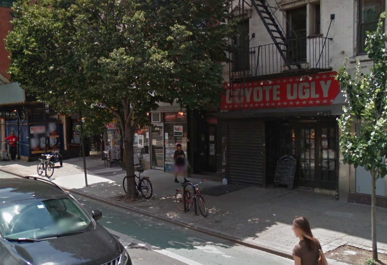 """A bar with the protective grate pulled down and large lettering on a red sign above that reads """"Coyote Ugly"""""""