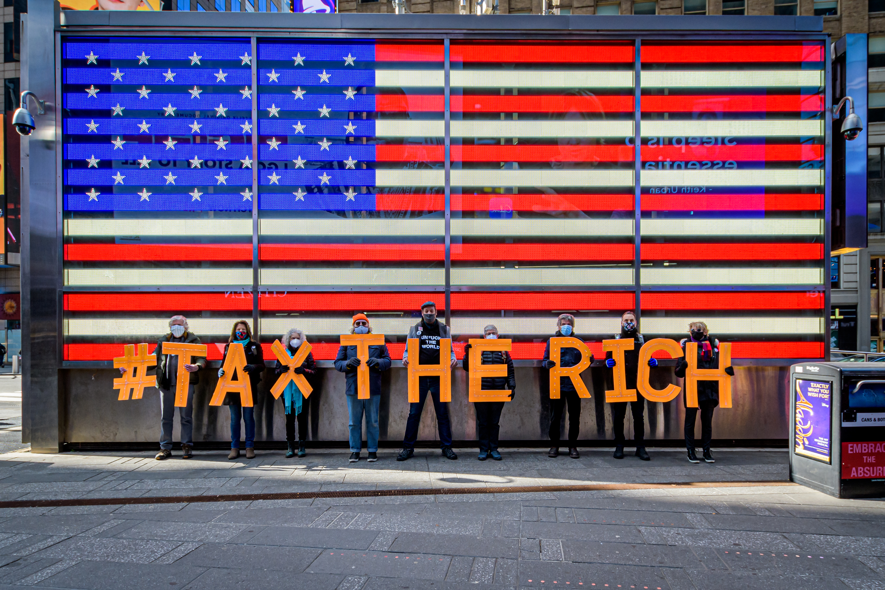 Participants seen spelling out #TaxTheRich at Times Square in front of an American flag.