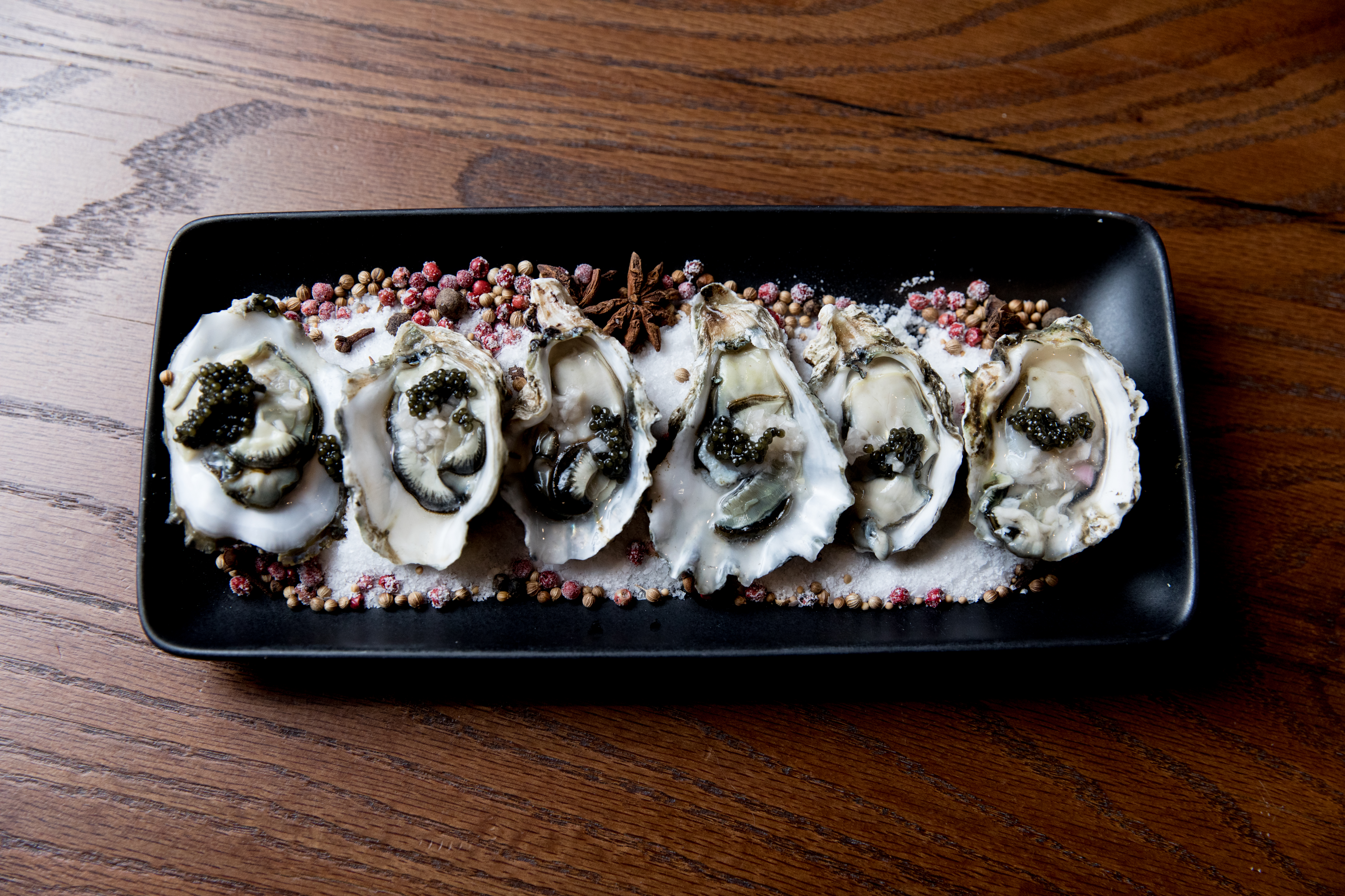 A black serving platter displays a row of six oysters with champagne mignonette