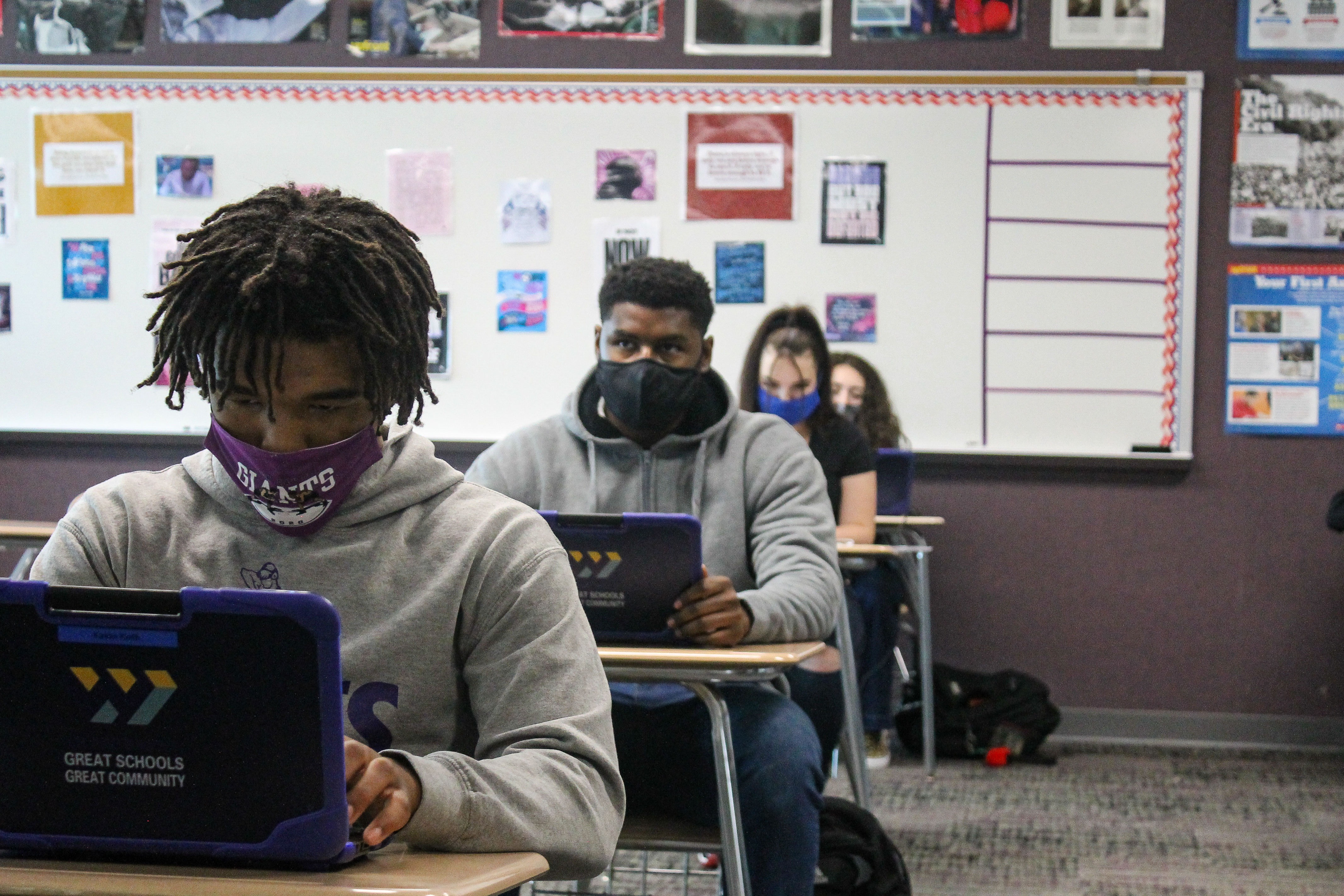 A row of masked students at Ben Davis High School in Indianapolis, Ind.,work on laptops in c classroom, with a white board behind them.