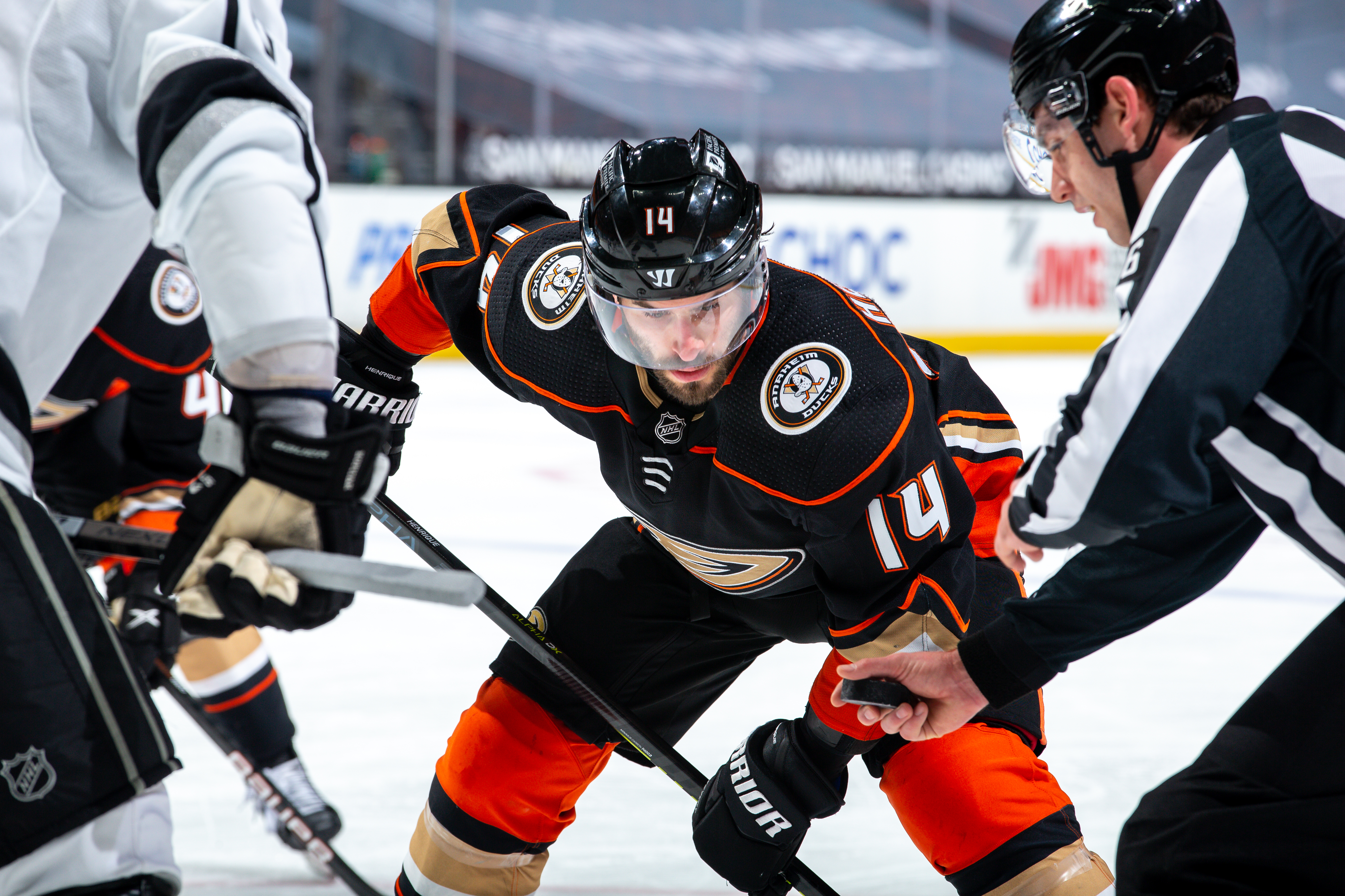 Adam Henrique #14 of the Anaheim Ducks waits for a face-off as linesman Jesse Marquis #86 prepares to drop the puck at Honda Center on March 10, 2021 in Anaheim, California.