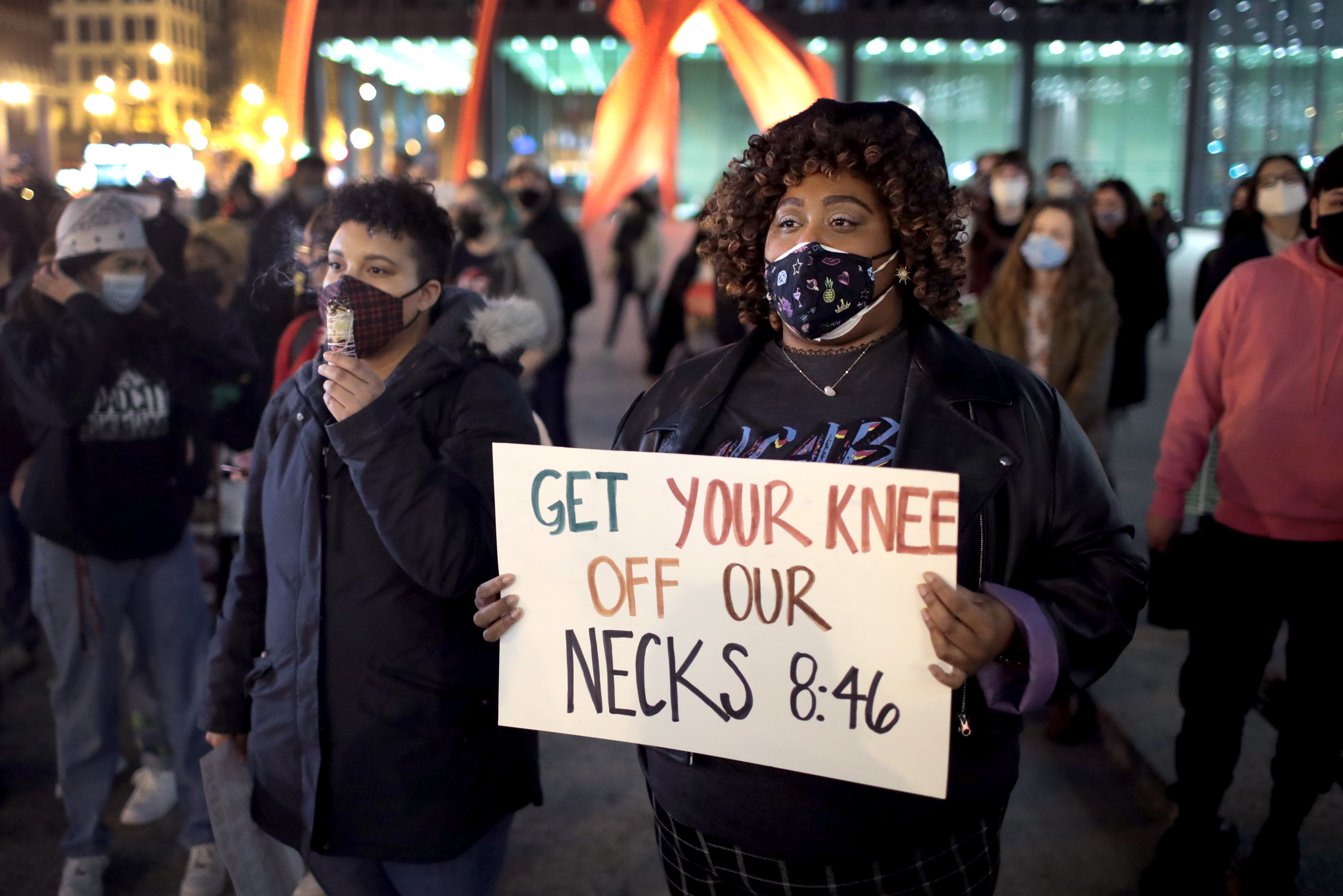 "Chicago demonstrator holds sign reading ""Get your knees off our necks"""