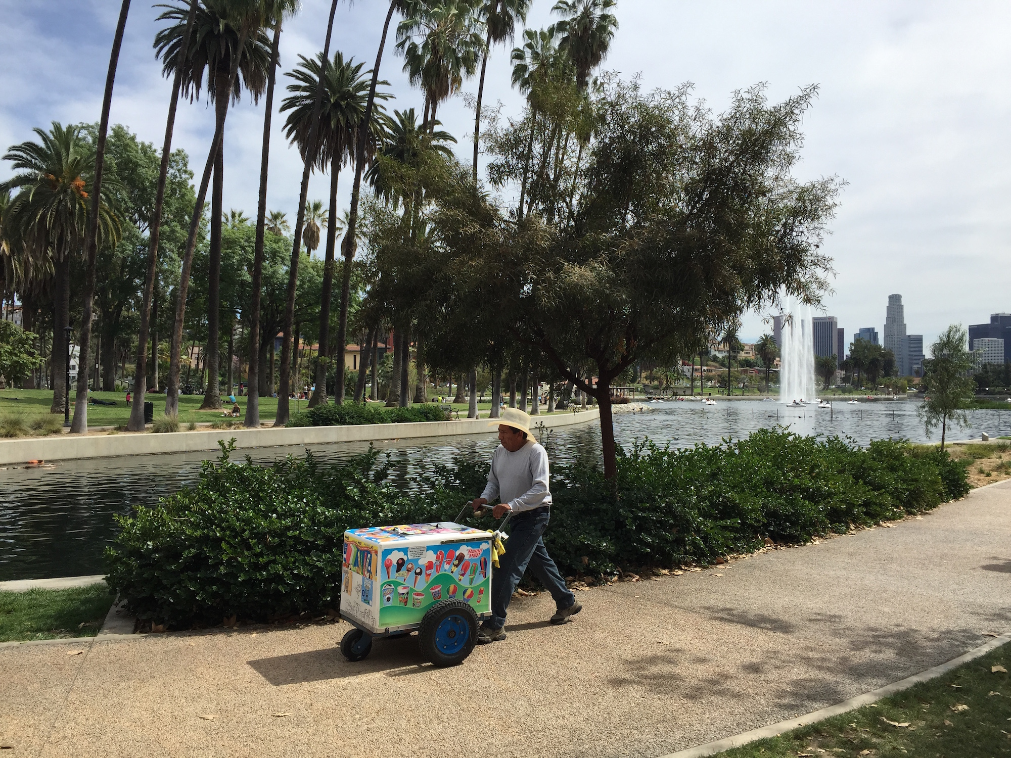 A vendor sells at Echo Park Lake on a sunny day, pushing a cart of paletas.