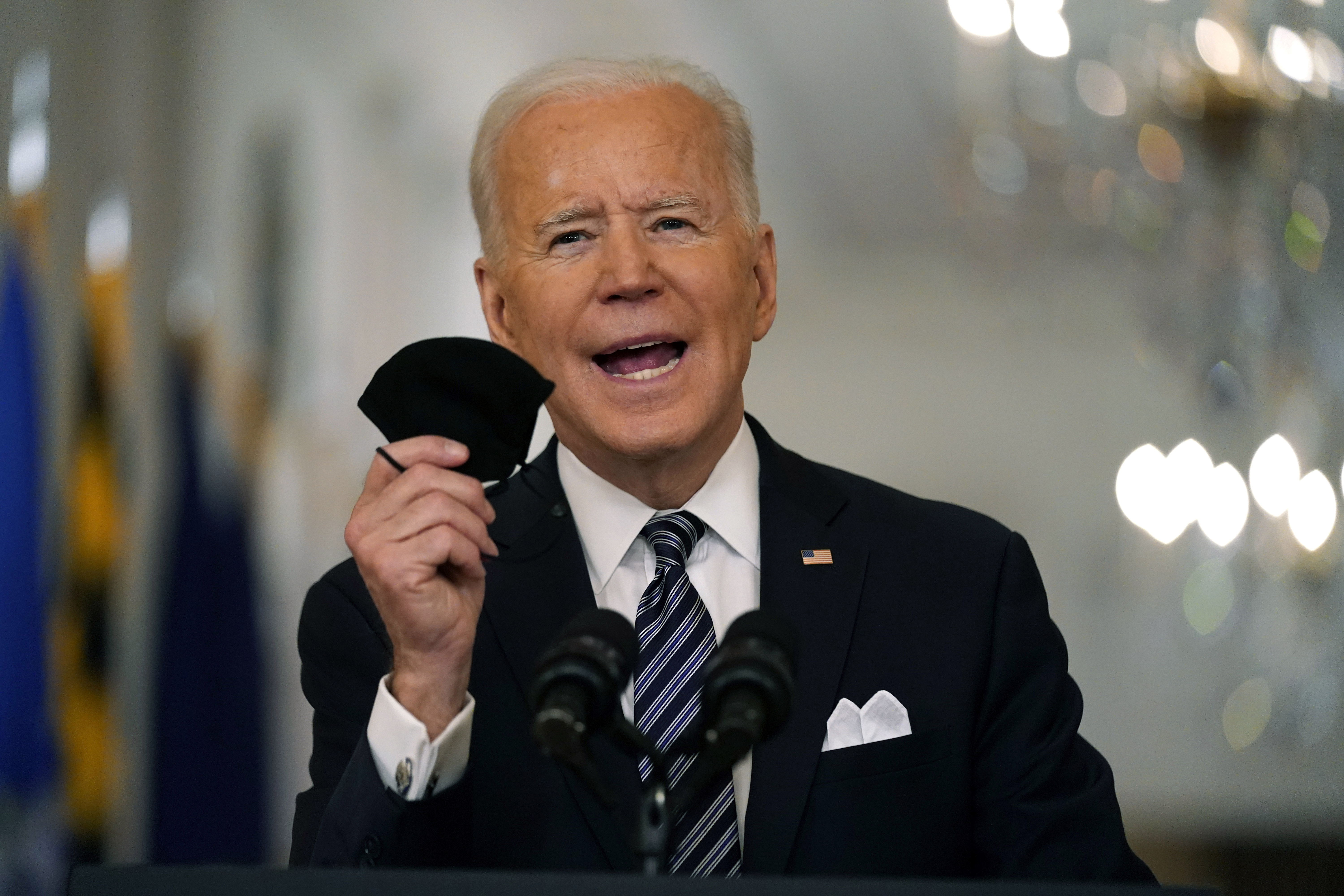 In this March 11, 2021, file photo, President Joe Biden holds up his face mask as he speaks about the COVID-19 pandemic during a prime-time address from the East Room of the White House in Washington.