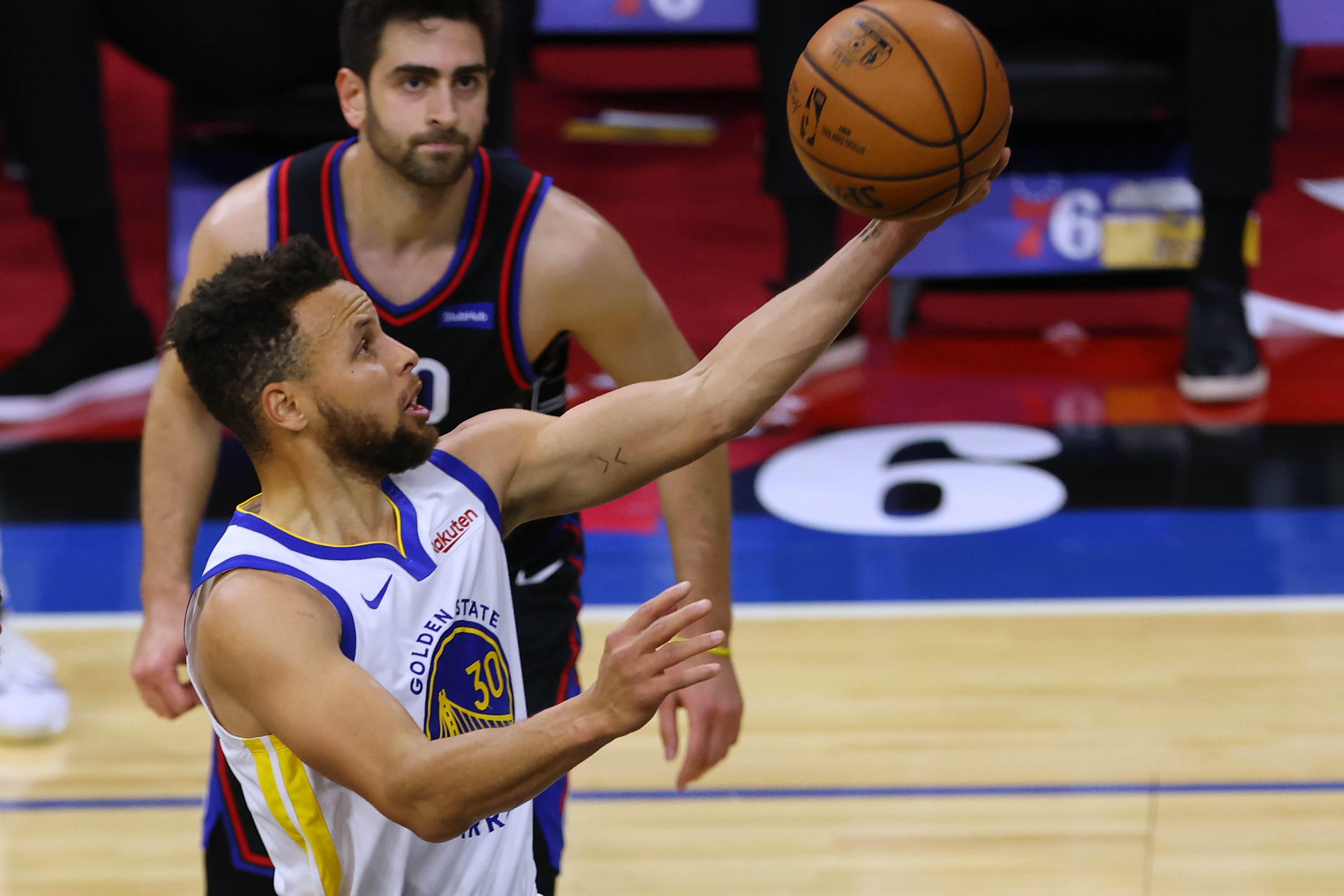 Stephen Curry of the Golden State Warriors in action against Furkan Korkmaz and Mike Scott of the Philadelphia 76ers during an NBA basketball game at Wells Fargo Center on April 19, 2021 in Philadelphia, Pennsylvania. The Warriors defeated the 76ers 107-96.