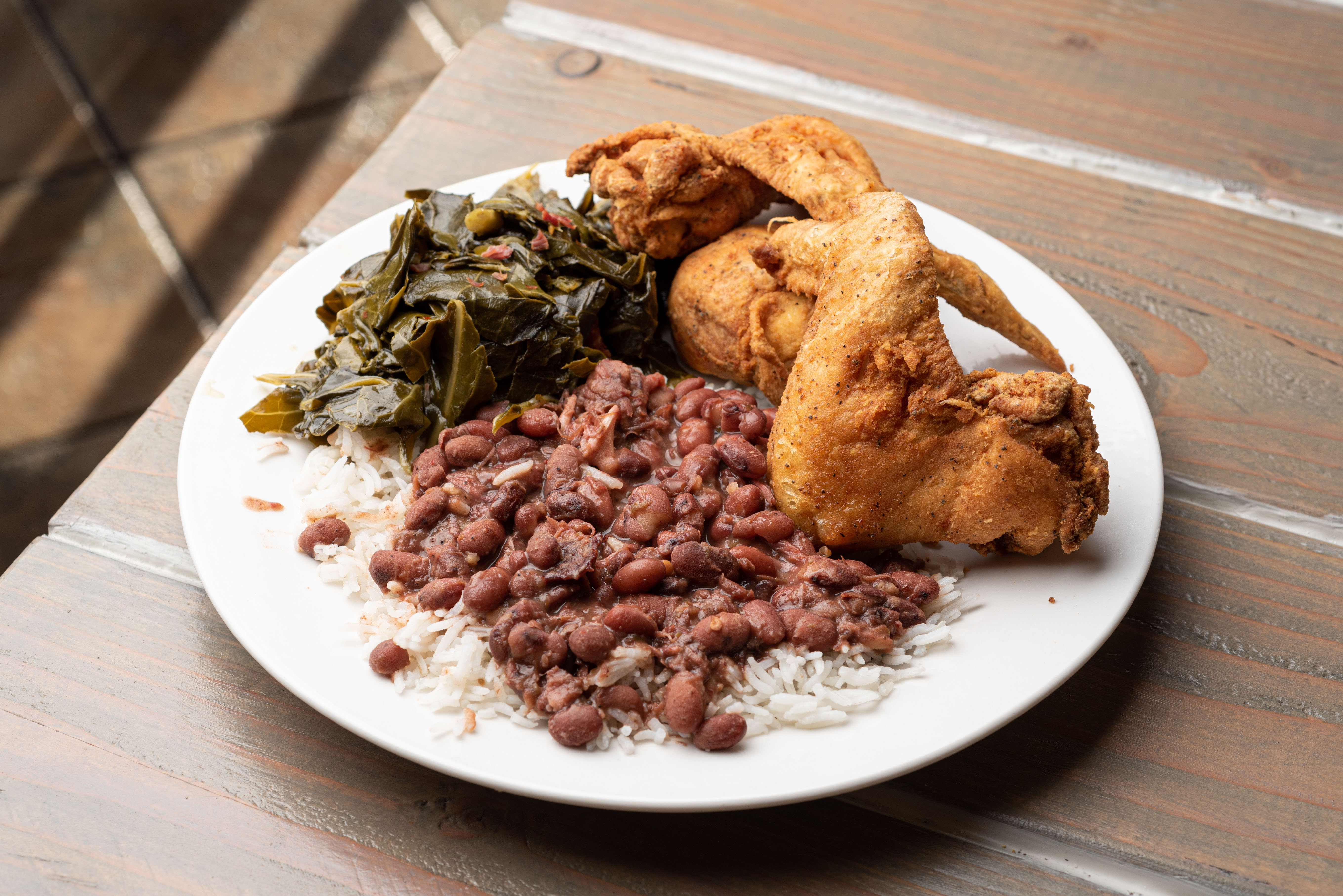 A plate of fried chicken with collard greens and red beans atop rice.