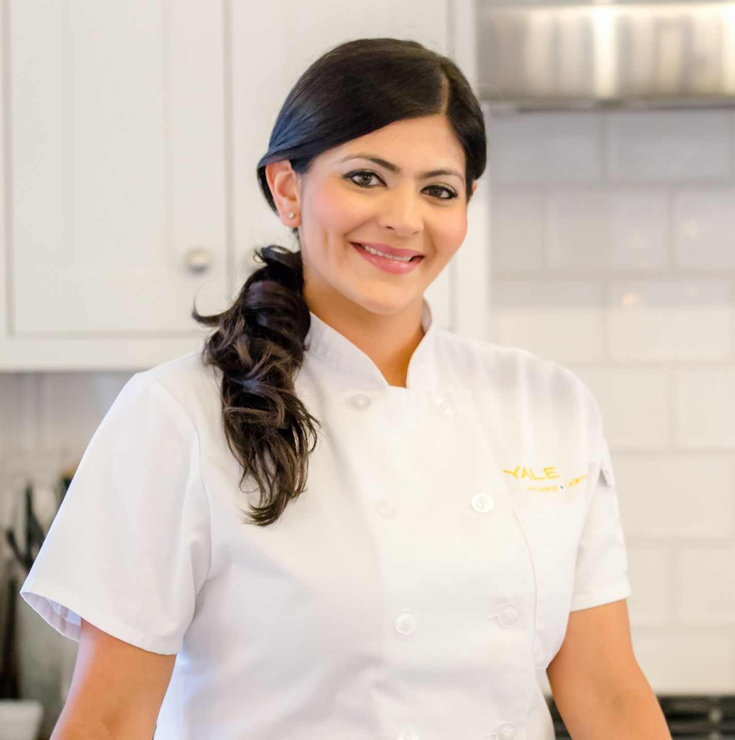Framingham-born cook and food TV personality Saba Wahid stands in a kitchen in her chef's whites, smiling as she looks directly into the camera
