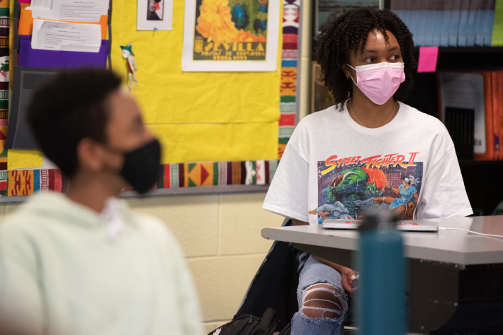 Students sit in a Chicago classroom, both with a mask on and a yellow bulletin board behind them. One student is in the foreground but blurry, the student in the background is sharper in the image.