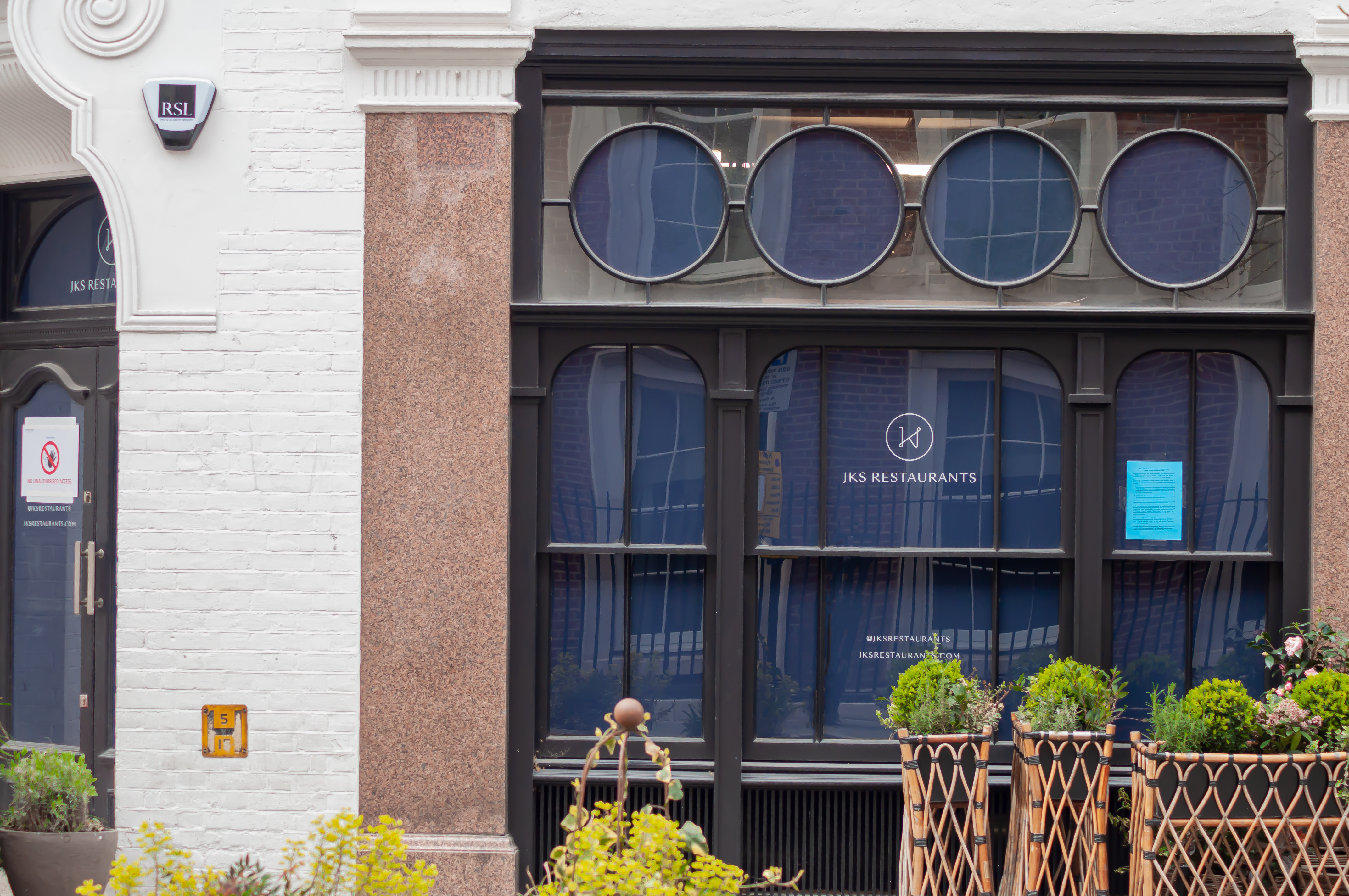 """""""JKS Restaurants"""" signage in the windows of a new restaurant at 42 North Audley Street in Mayfair"""