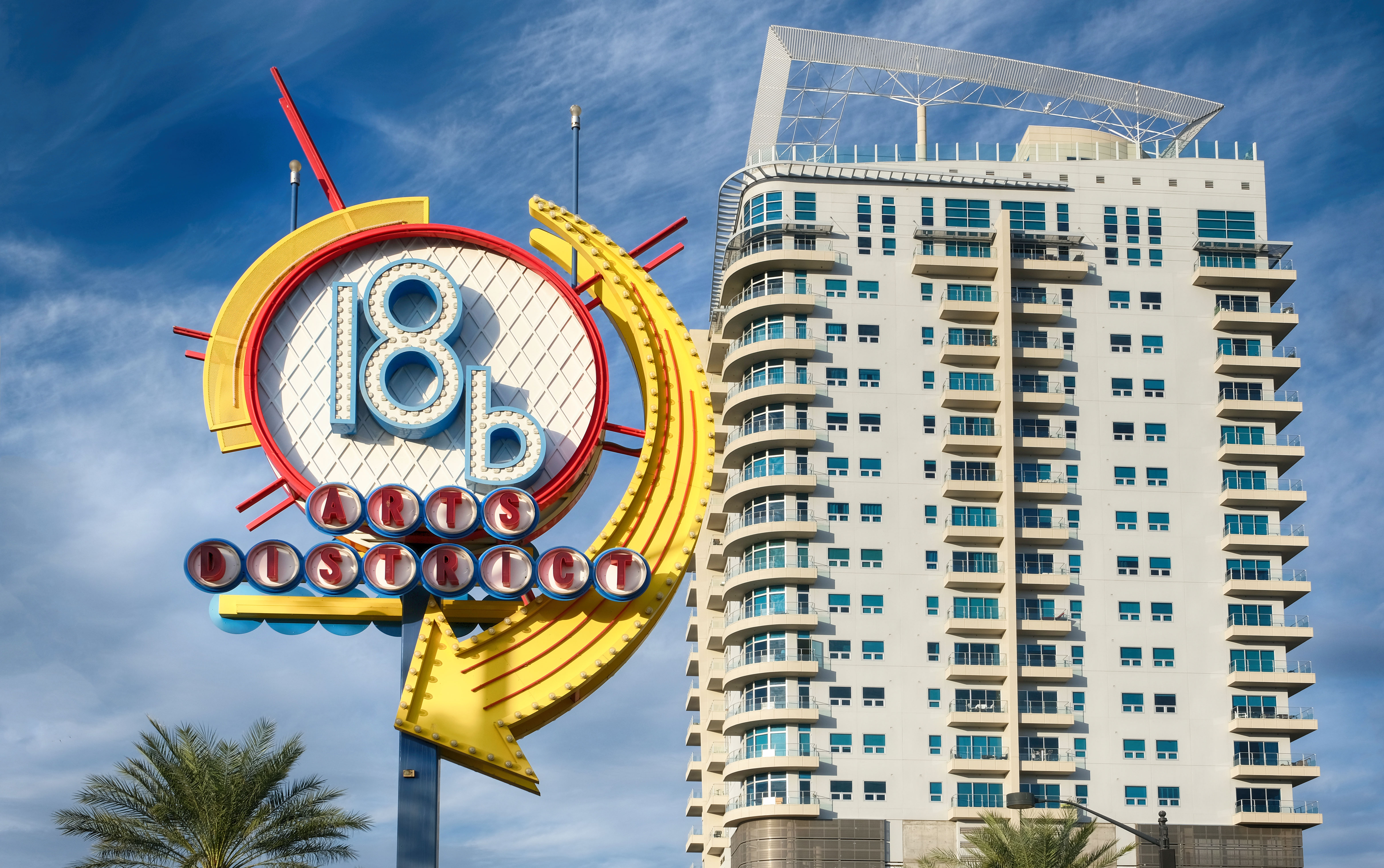 A round neon sign with an apartment tower in the background