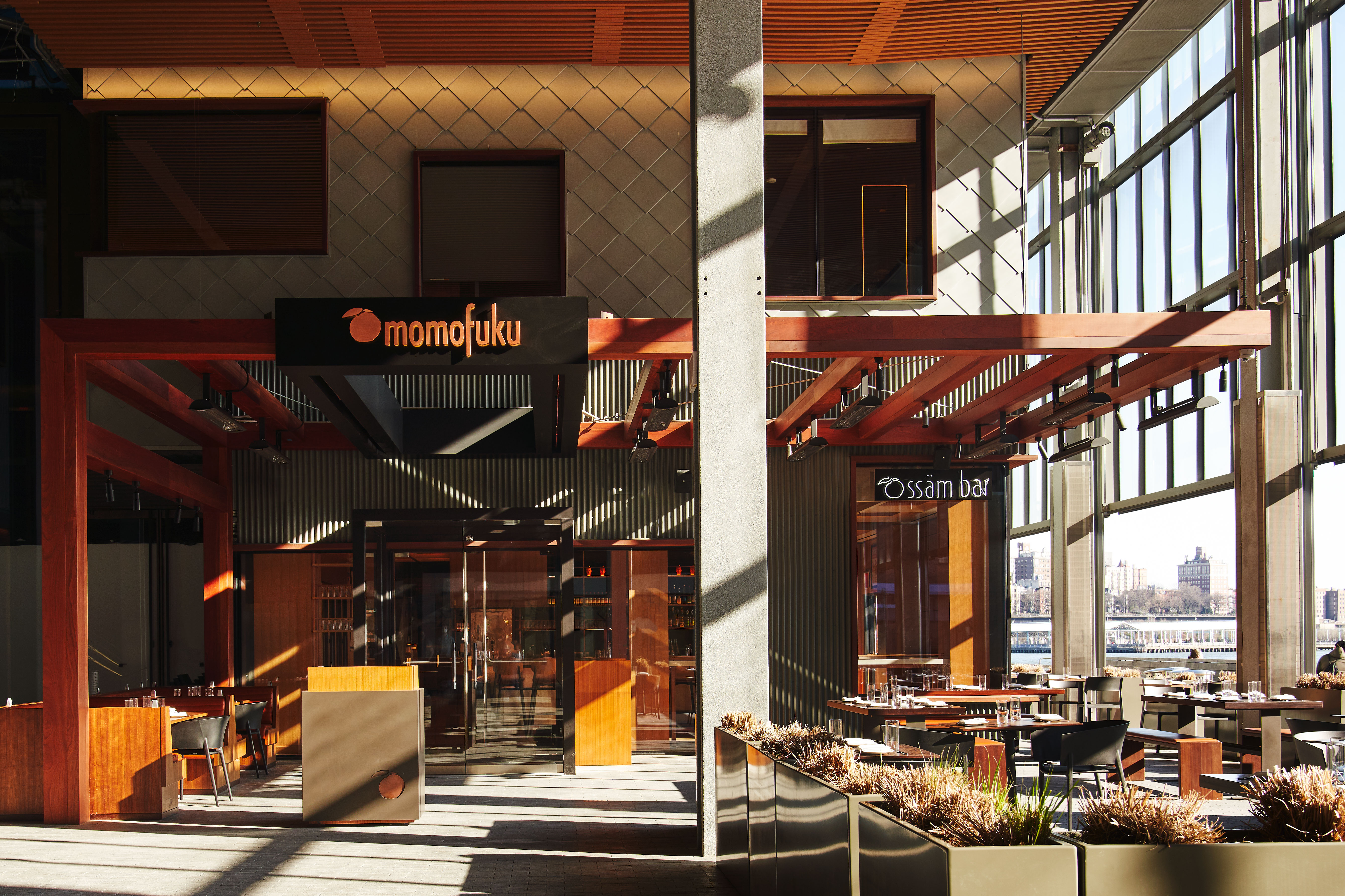 A exterior photo of the restaurant with sun streaming in through large windows and a patio set up out front