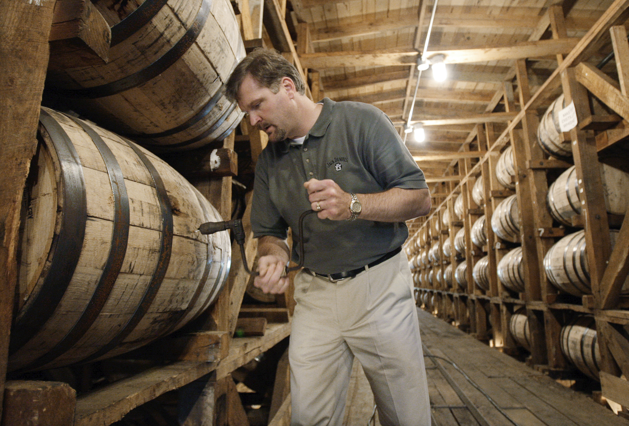 Jeff Arnett, the master distiller at the Jack Daniel Distillery in Lynchburg, Tennessee., drills a hole in a barrel of whiskey in one of the aging houses at the distillery in 2009.