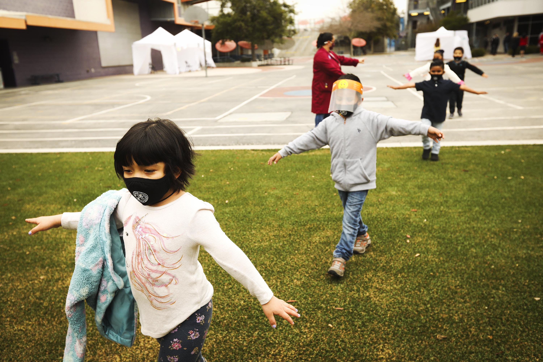 Children wearing face masks walk in a distanced line across a school's grounds.