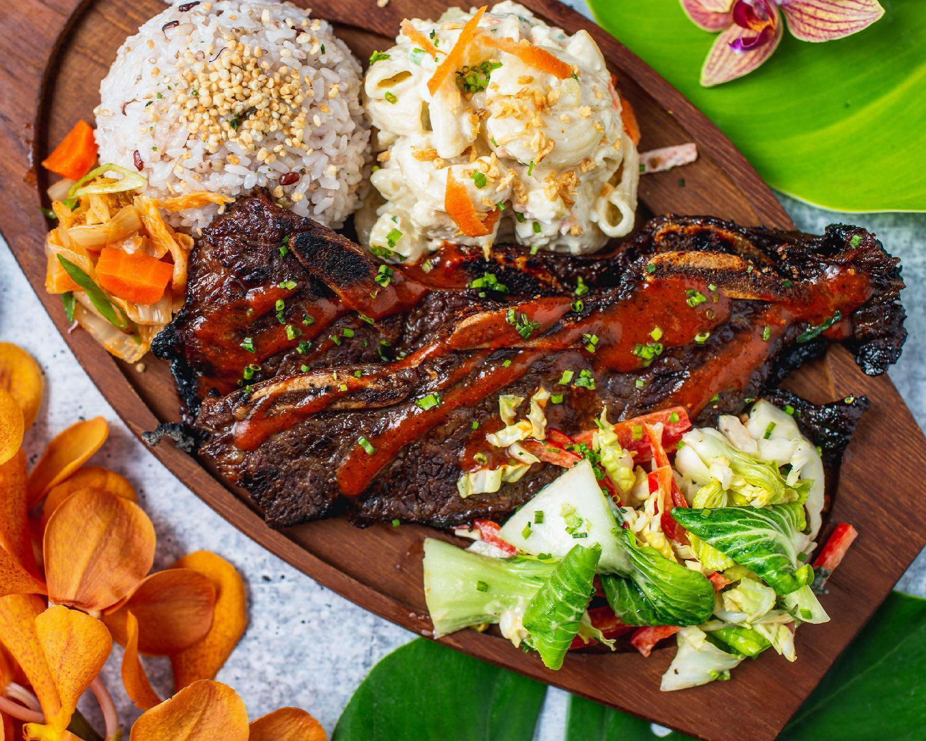 A wooden platter holds macaroni salad, rice, and short ribs with a spicy sauce at Da Pine Grinds