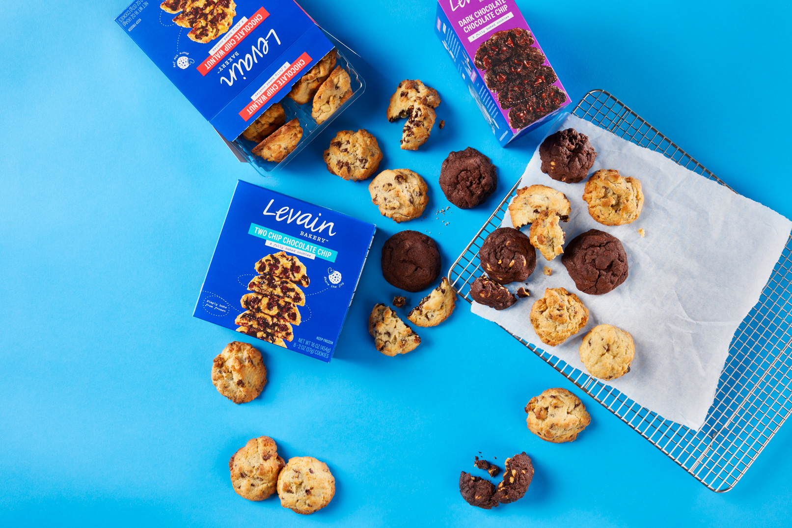 """An overhead shot of three types of cookies spilling out from boxes marked """"Levain"""" on a blue background"""