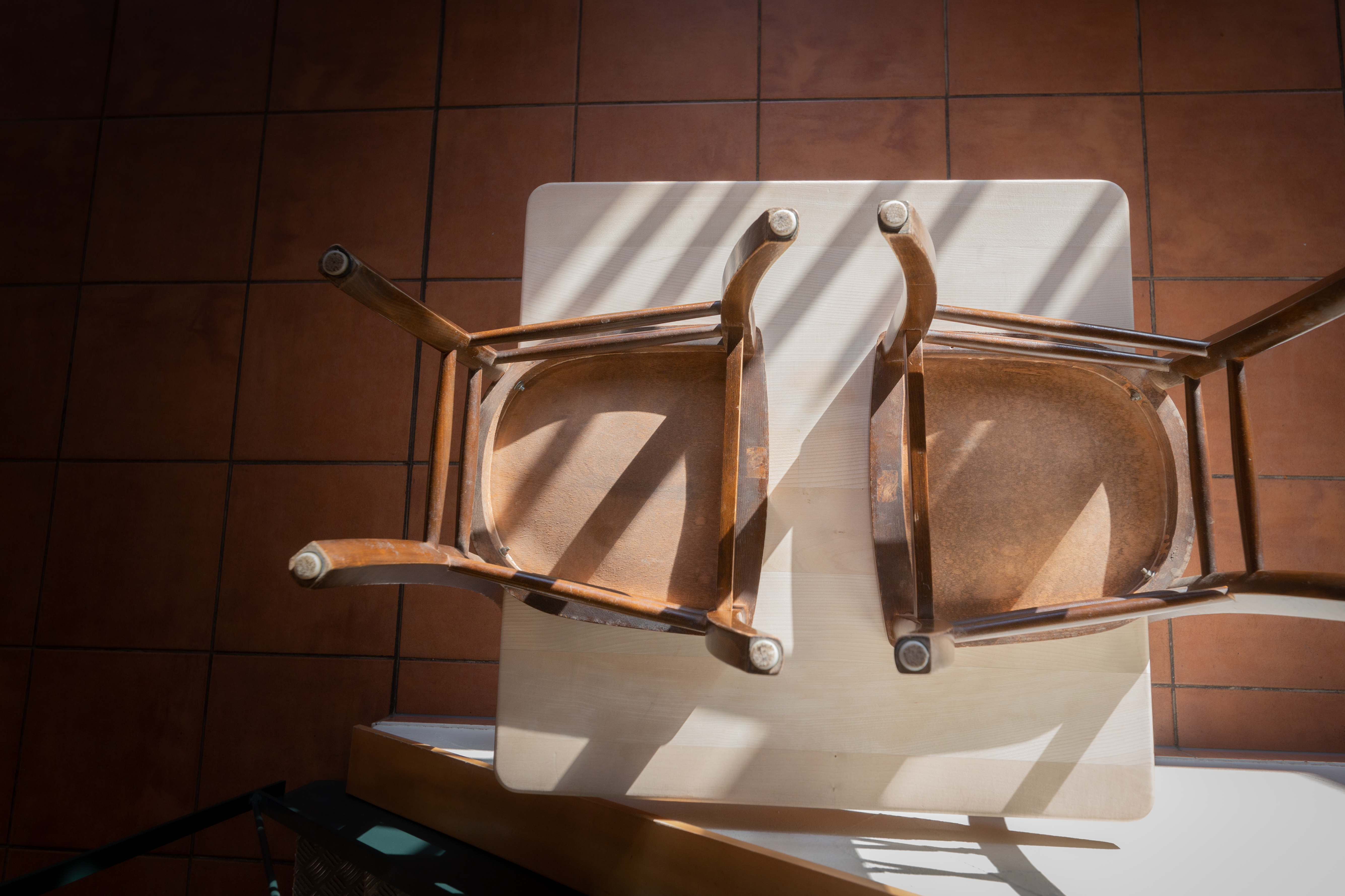 An empty restaurant table with two chairs overturned