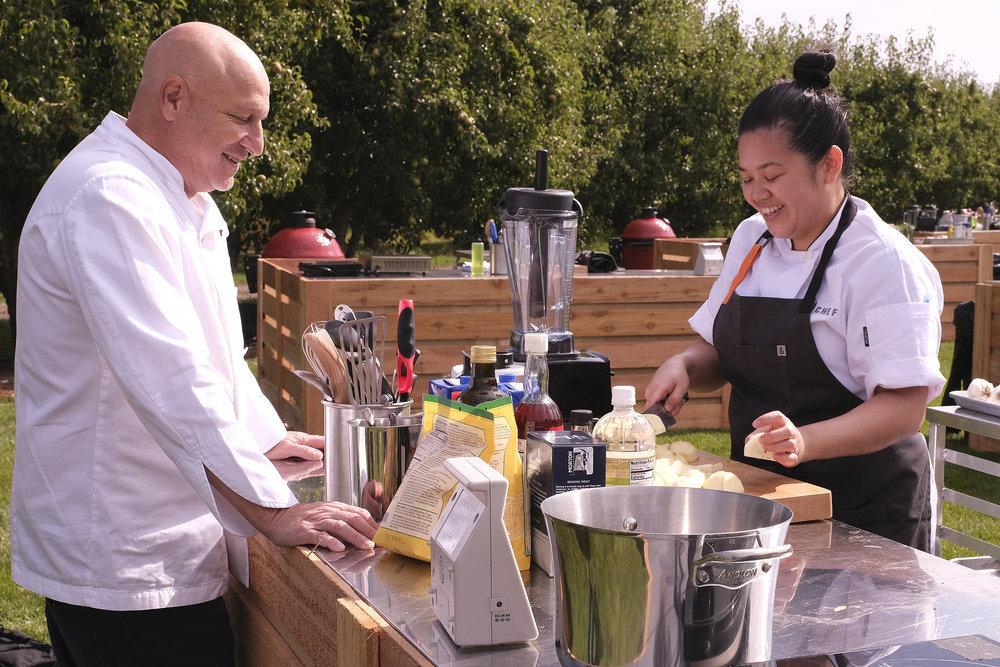A man in a chef's coat talks to a woman in an apron