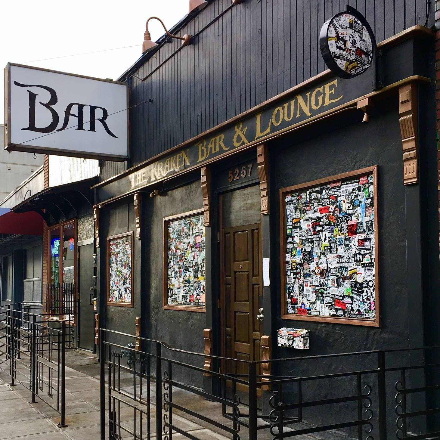 """The exterior of The Kraken Bar & Lounge in the U District, with a sign that says """"Bar"""" and the name emblazoned in gold lettering out front"""