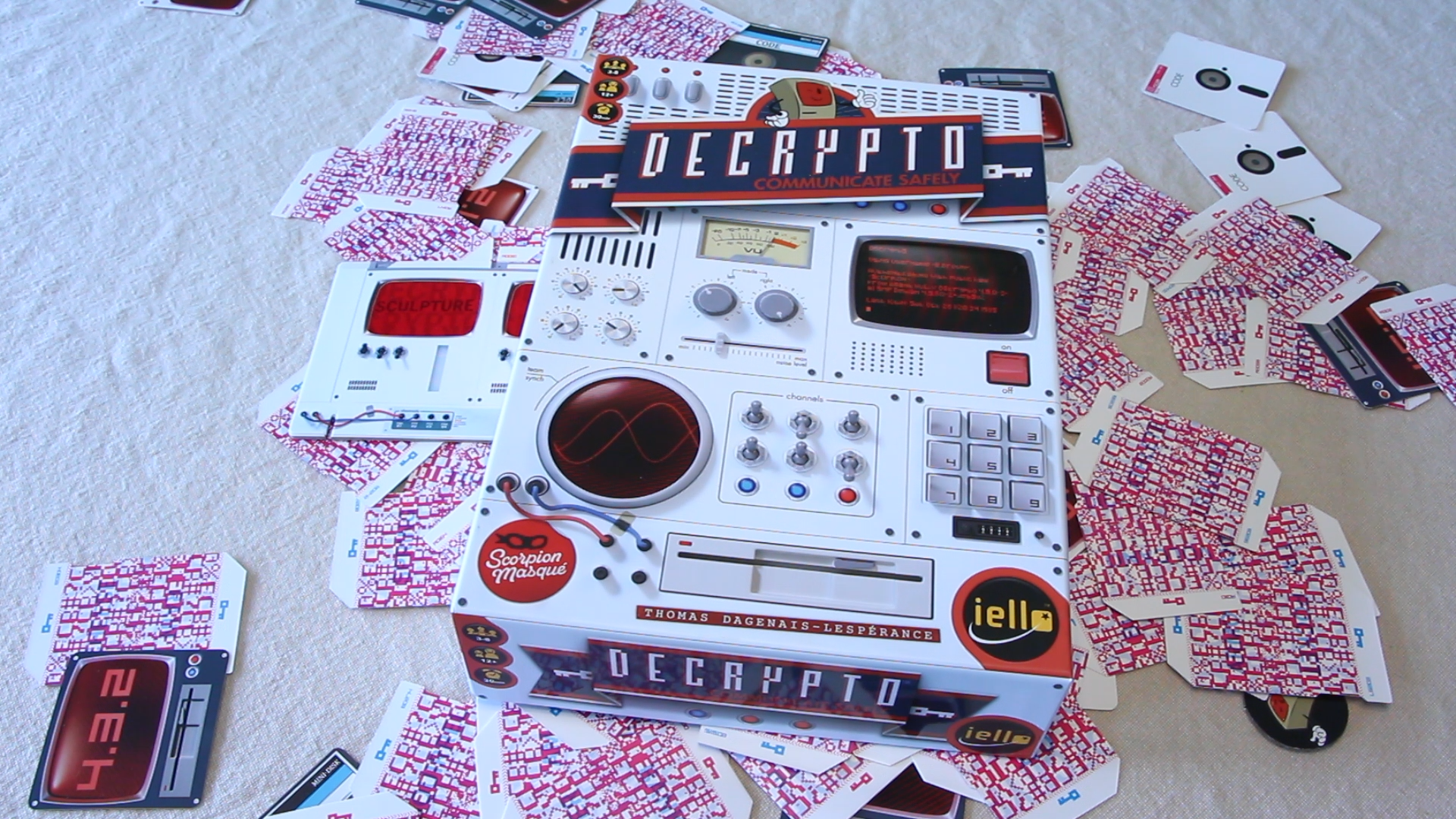 The box for the board game Decrypto sits at top a pile of the games cards and components.