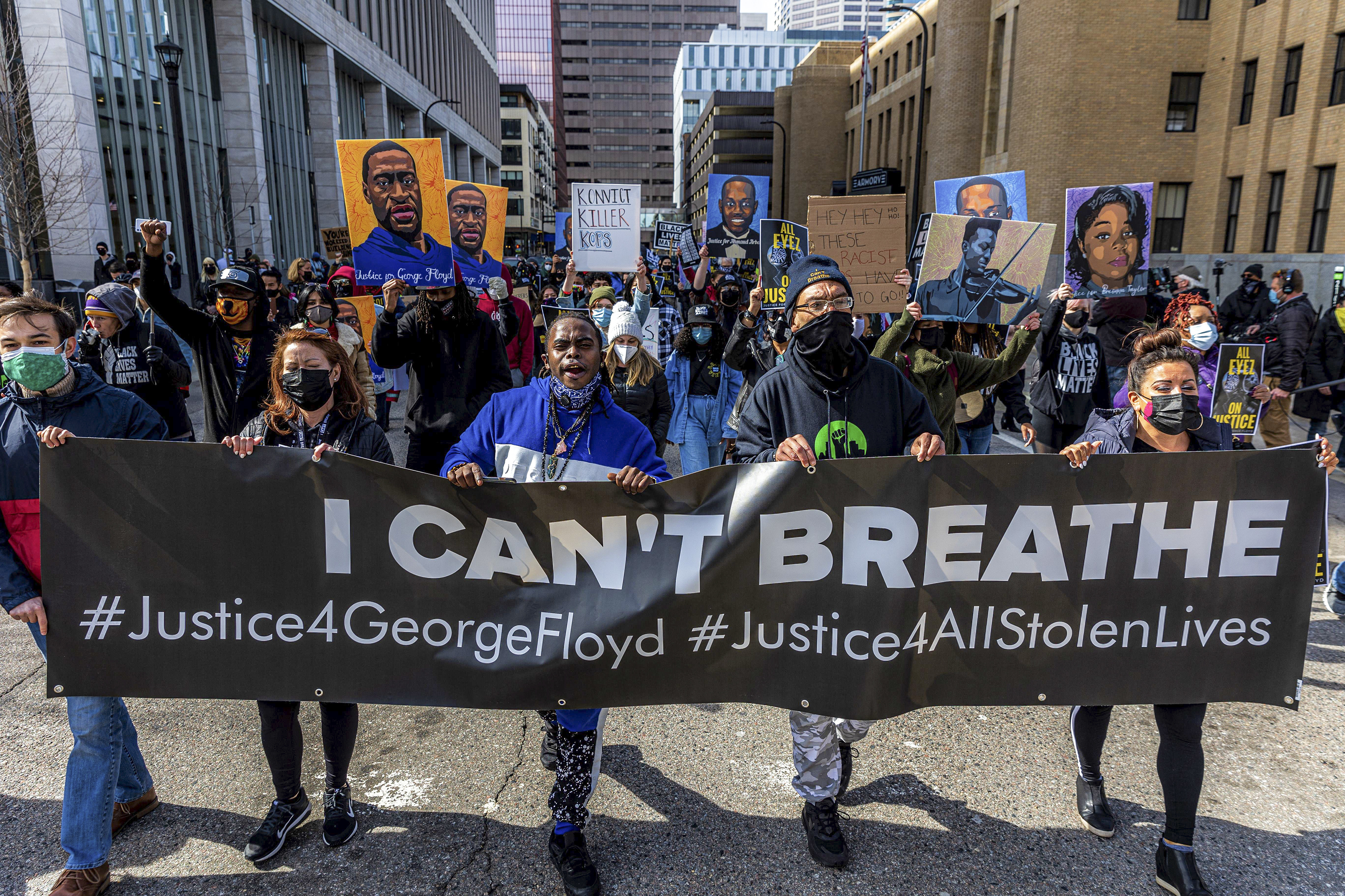 """A dense, but socially distanced crowd carries paintings of George Floyd and Breonna Taylor behind a line of masked protesters who, together, are carrying a banner that reads, """"I can't breathe, justice for George Floyd, justice for all stolen lives."""""""