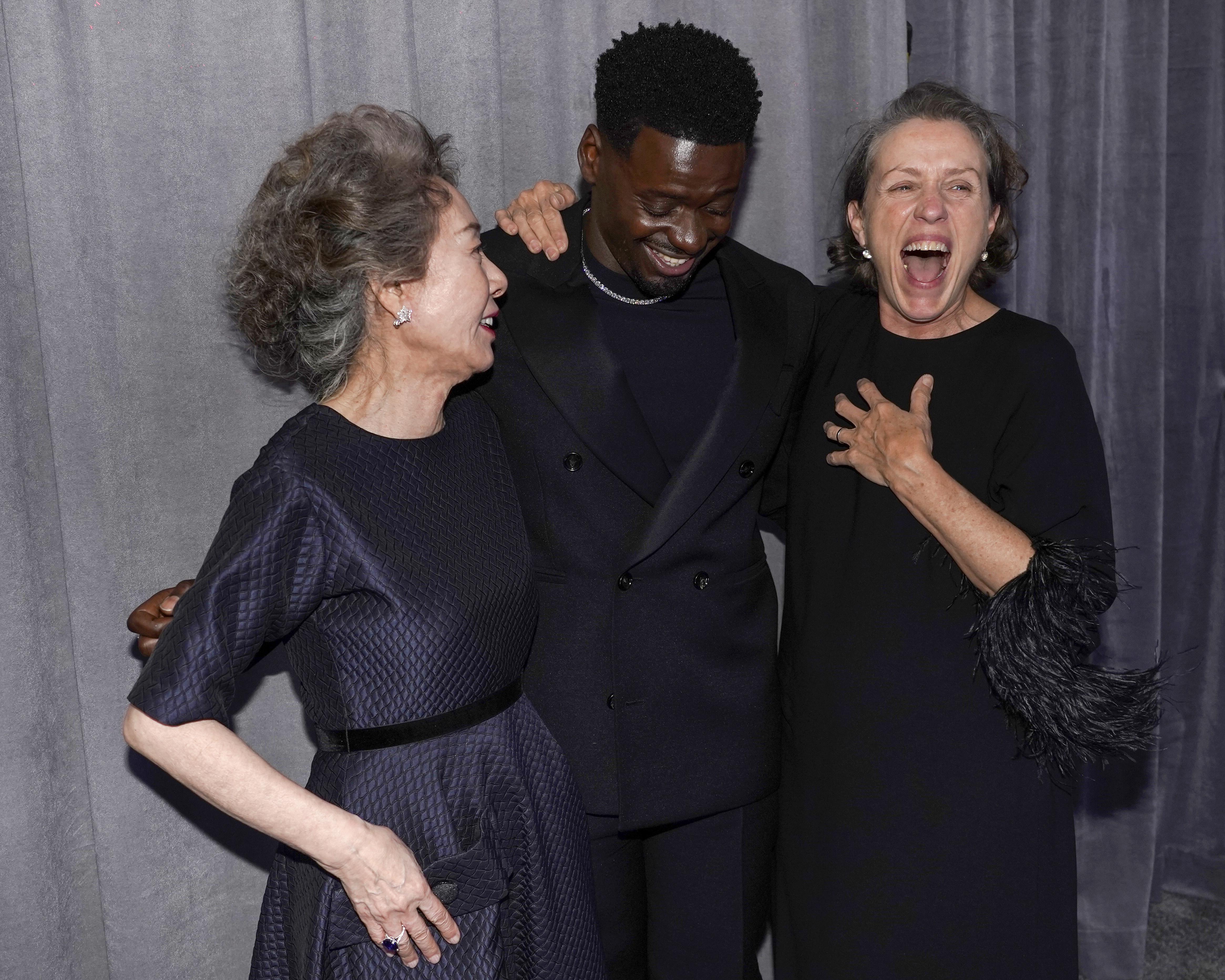 Yuh-Jung Youn, Daniel Kaluuya, and Frances McDormand laugh together after their 2021 Oscar wins